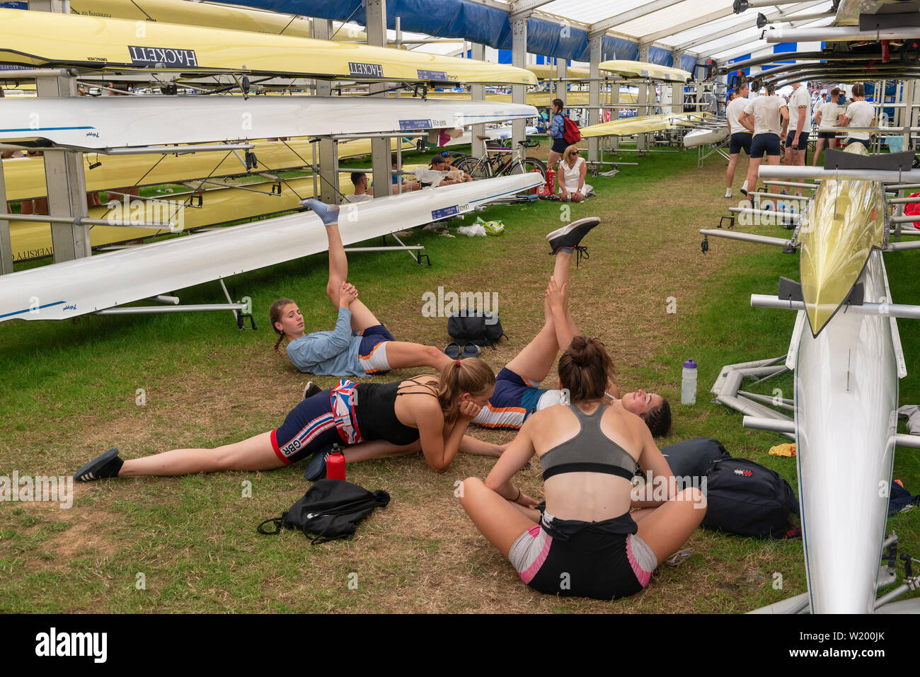 Henley on Thames, Berkshire, UK. 4th July, 2019. Henley Royal Regatta Girl competitors  limbering up with stretches in the boat tent before their afterrnoon race . Credit Gary Blake/Alamy Live - Stock Image