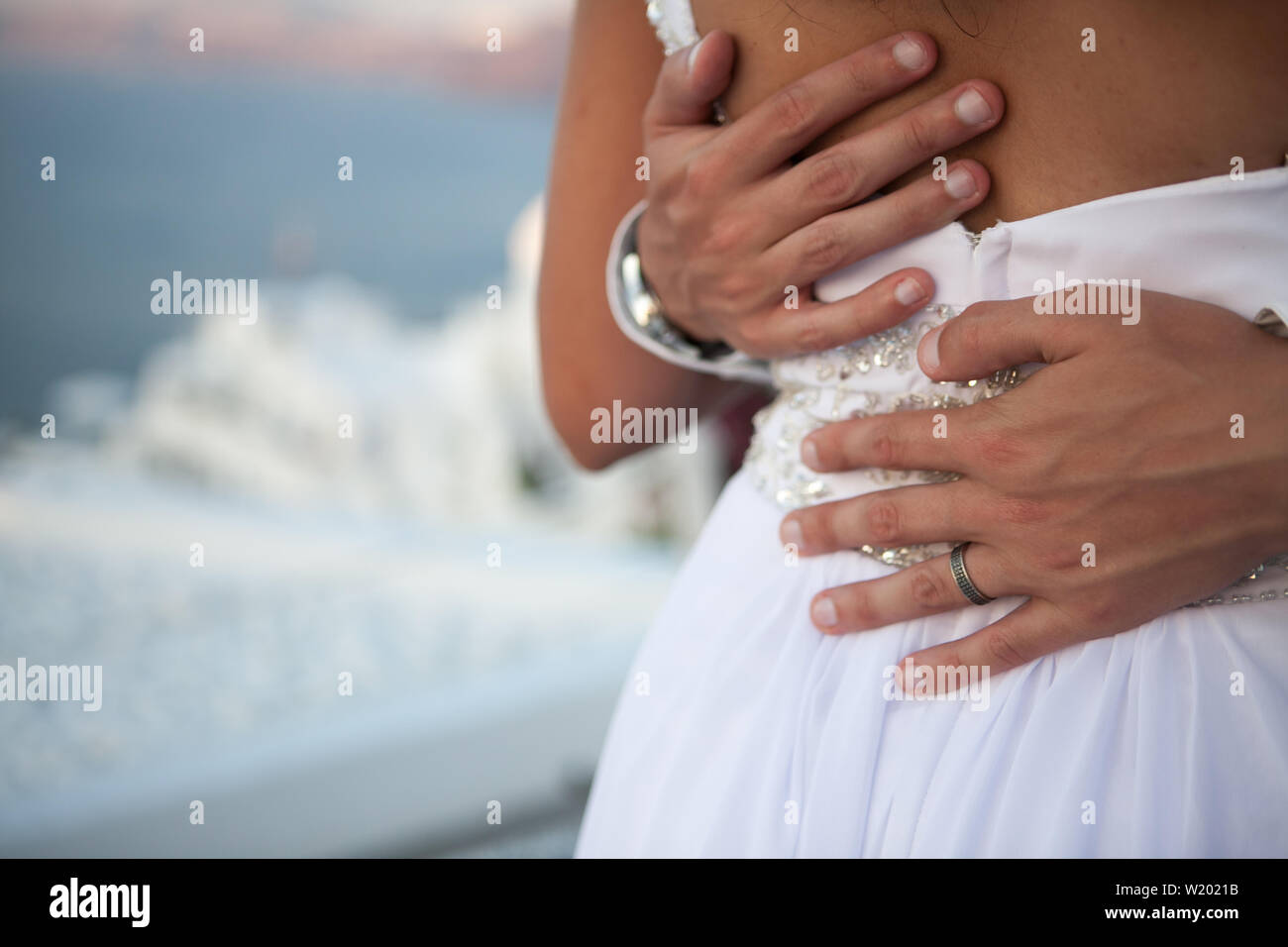 Closeup of mans hands with a wedding ring hugging the back of a woman against the background of a blurred sky and the city - Stock Image