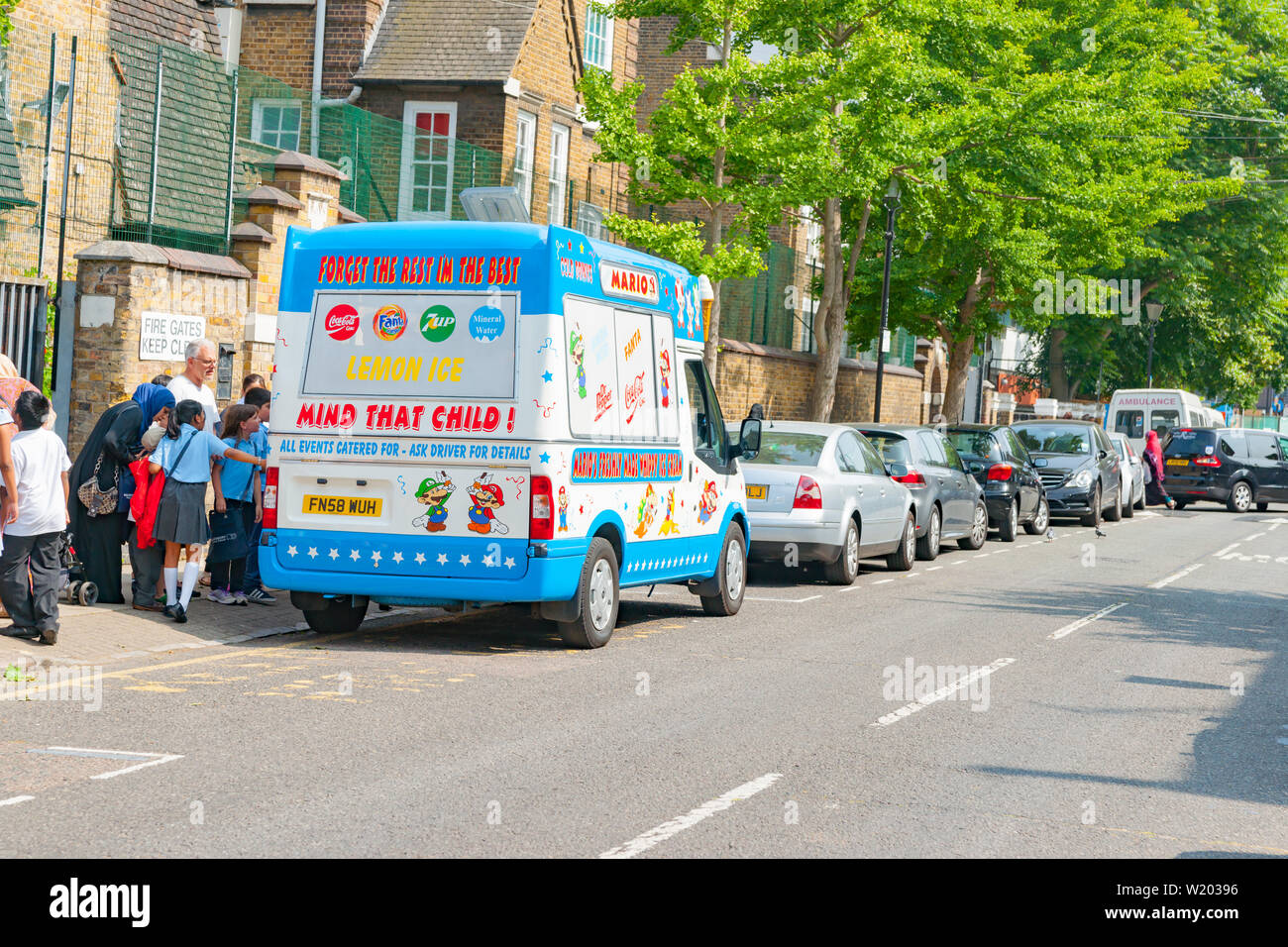 LONDON ENGLAND - JULY 13 2013; School children gather around ice-ceam truck with 'Mind that Child' sign after school in city typical street - Stock Image