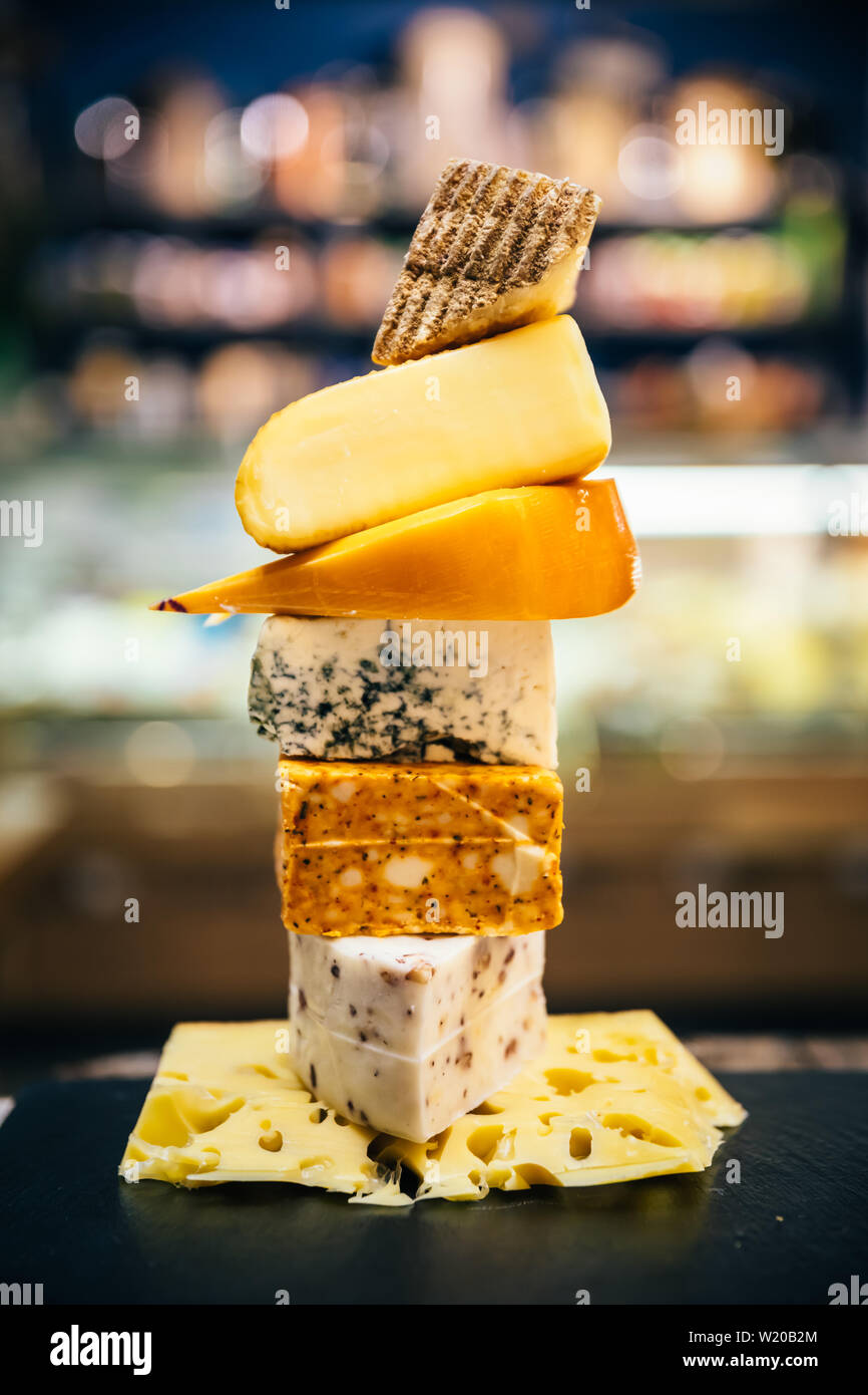 Assorted, various aged cheeses on plate or board. Different kind or type of delicious cheese on cheese platter. Stock Photo