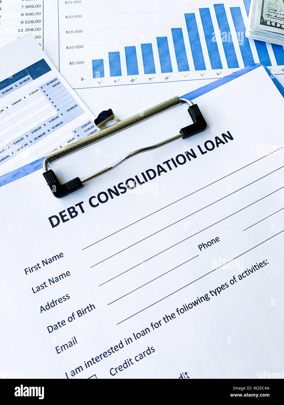 Debt consolidation loan document with graph on table. - Stock Image