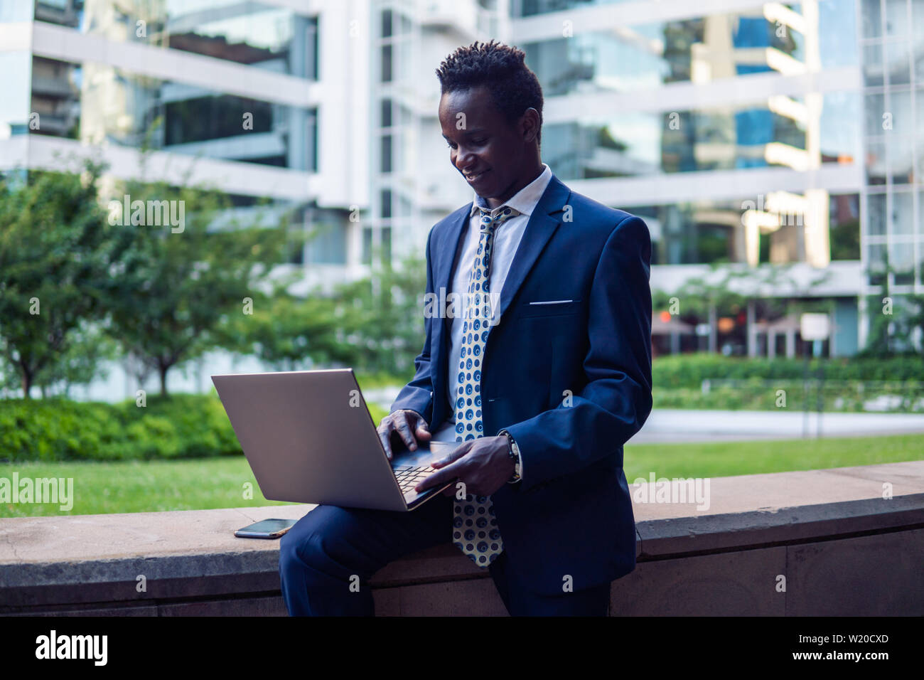 African American businessman holding laptop notebook wearing blue suit Stock Photo