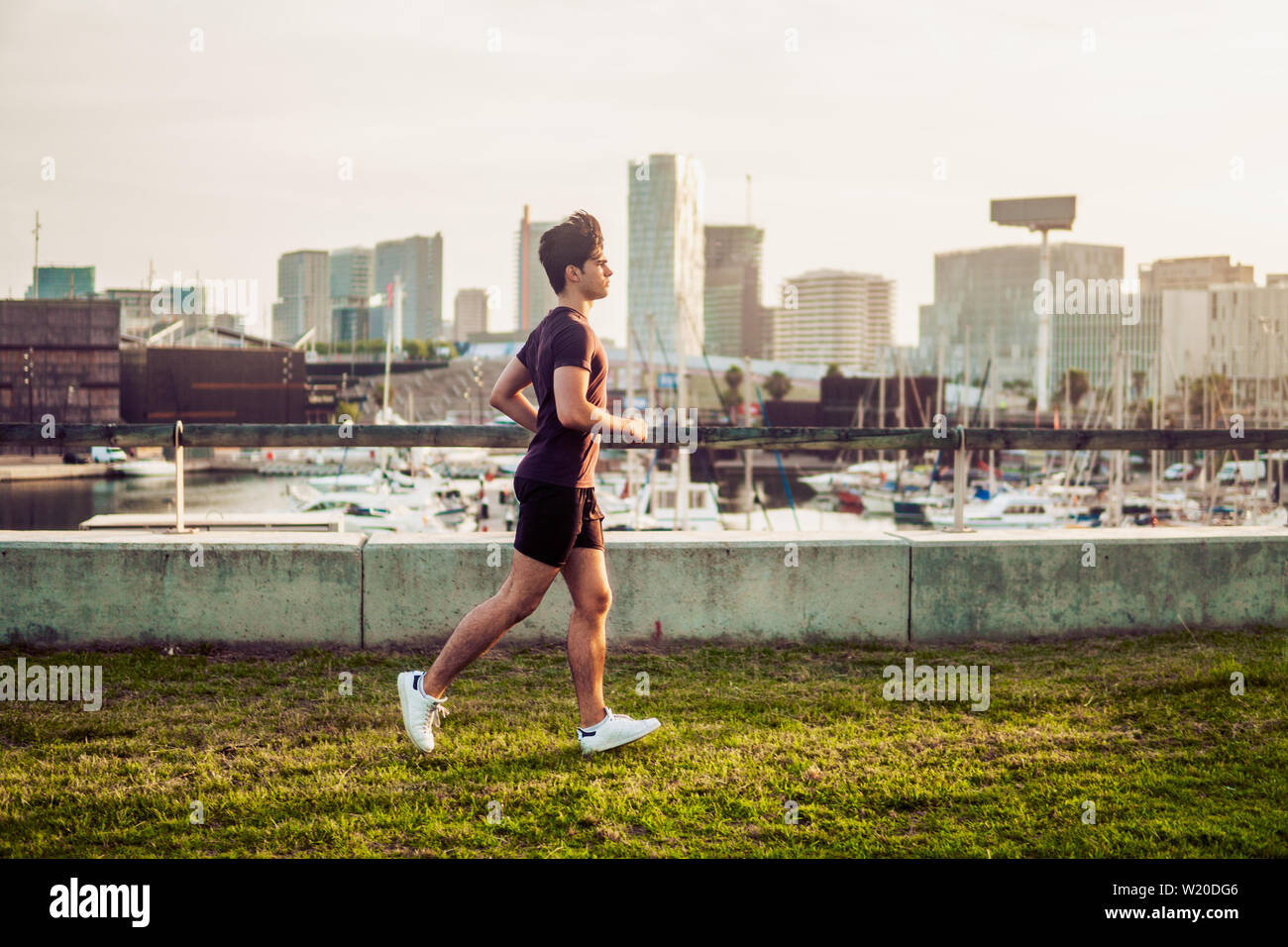 Young athletic man running at park with skyscrapers background Stock Photo
