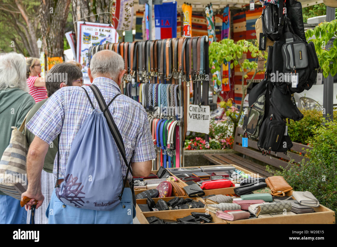 LENNO, LAKE COMO, ITALY - JUNE 2019: People looking at leather goods on a stall in the farmer's market in Lenno on Lake Como. - Stock Image