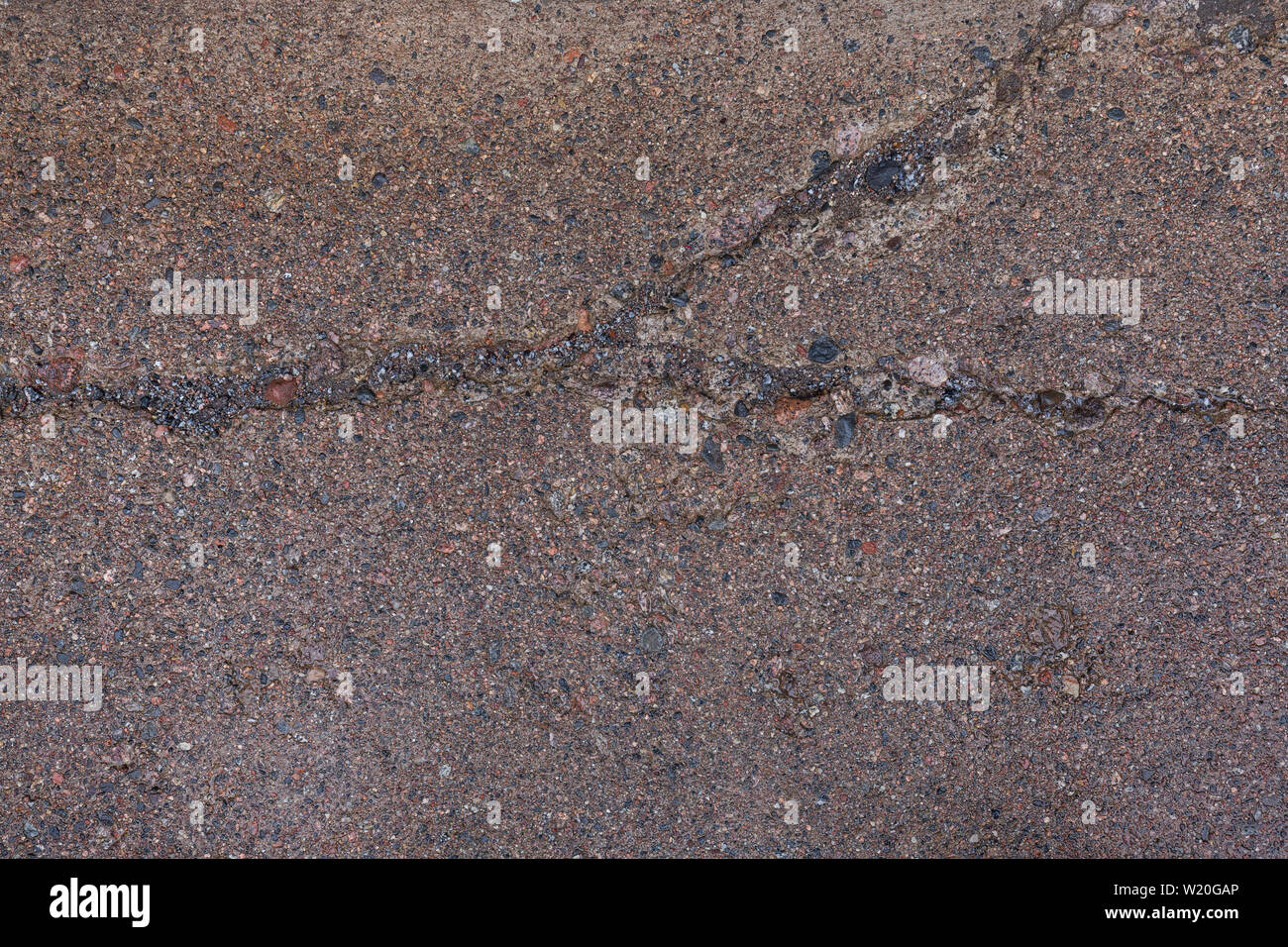 Close-up of a wet, weathered and cracked concrete footpath surface with pebbles (or pebblecrete or exposed aggregate) outdoors, viewed from above. Stock Photo