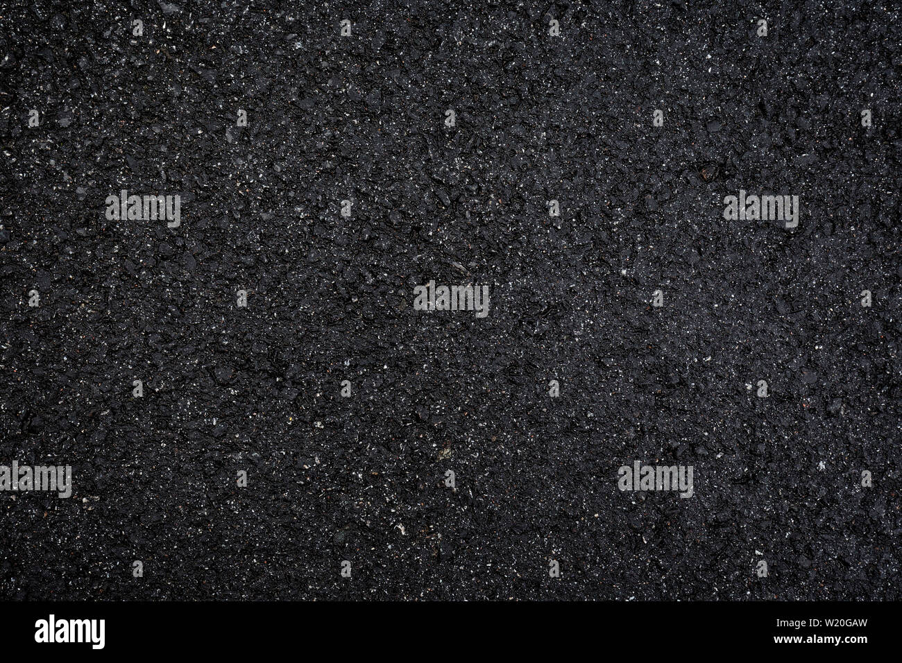 Close-up of wet, black asphalt, viewed from above. High resolution dark full frame textured background. Stock Photo