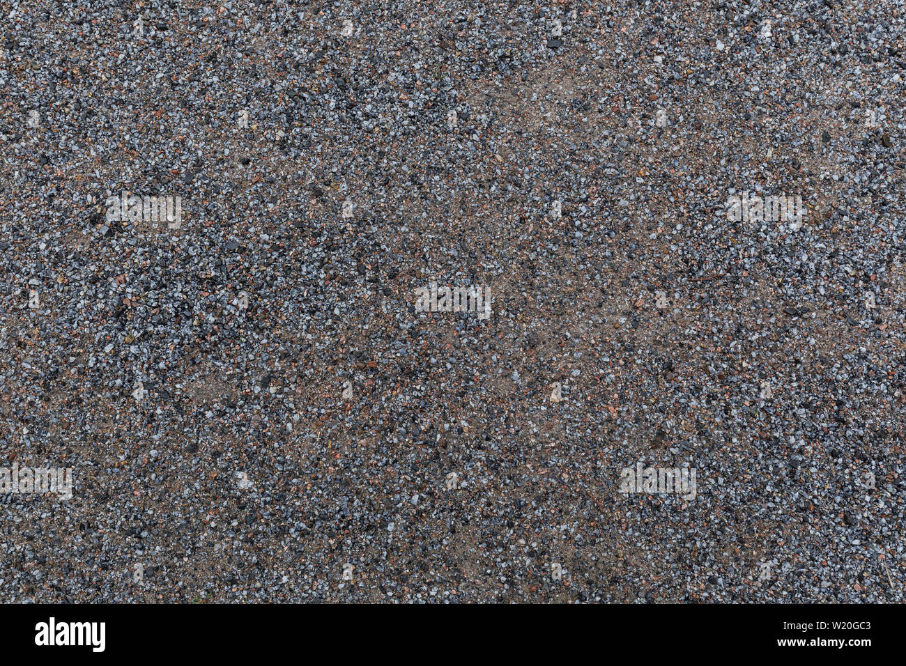 High resolution full frame textured background of wet sandy ground with gravel, viewed from above. Stock Photo