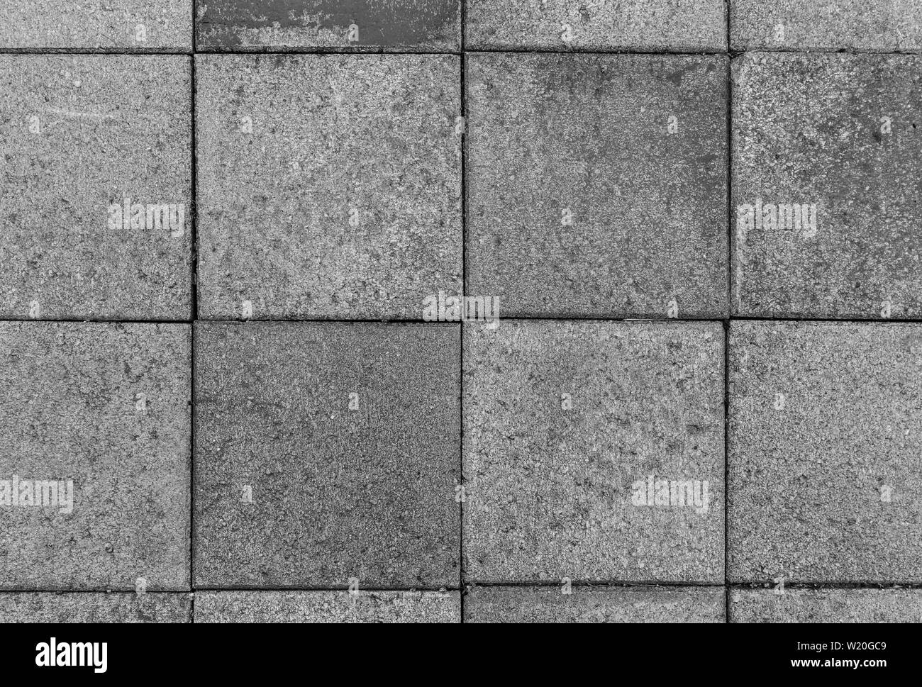 Close-up of a bit dirty and weathered square paving stones or blocks outdoors viewed from above in black & white. High resolution textured background. Stock Photo