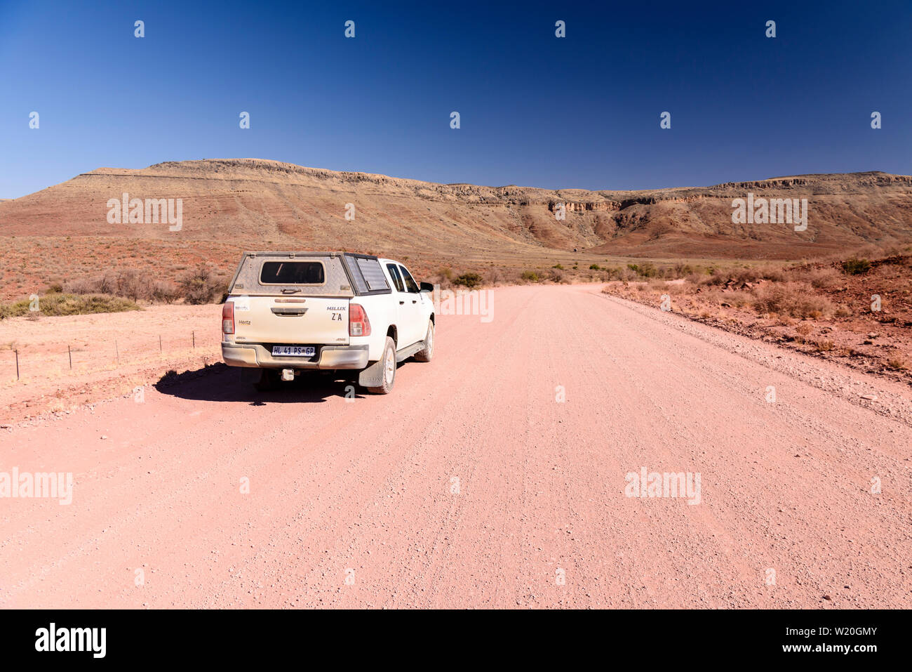 Toyota Hilux drives along a gravel dirt road leading towards mountains in Central Namibia Stock Photo