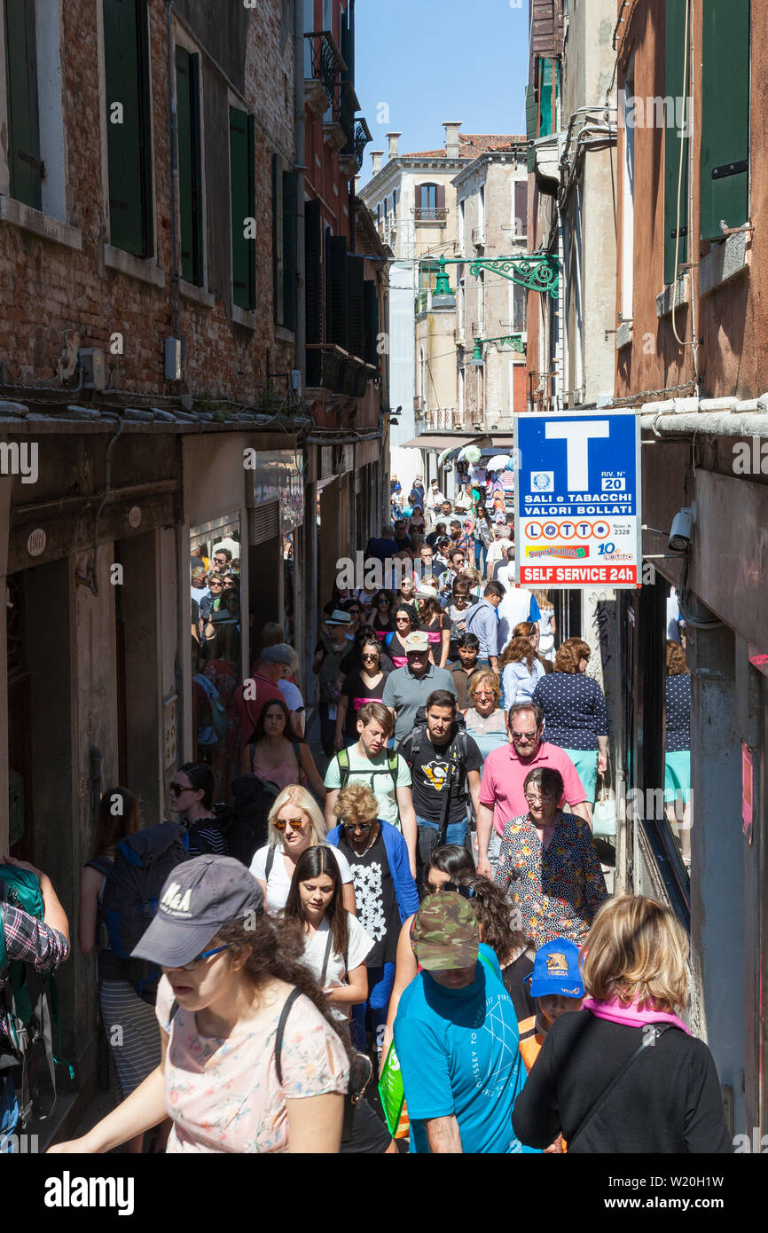 Unsustainable tourism Venice, Italy with a crowd  of tourists and locals jostling to pass in a bottleneck in Strada Nova, Cannaregio, route to station - Stock Image