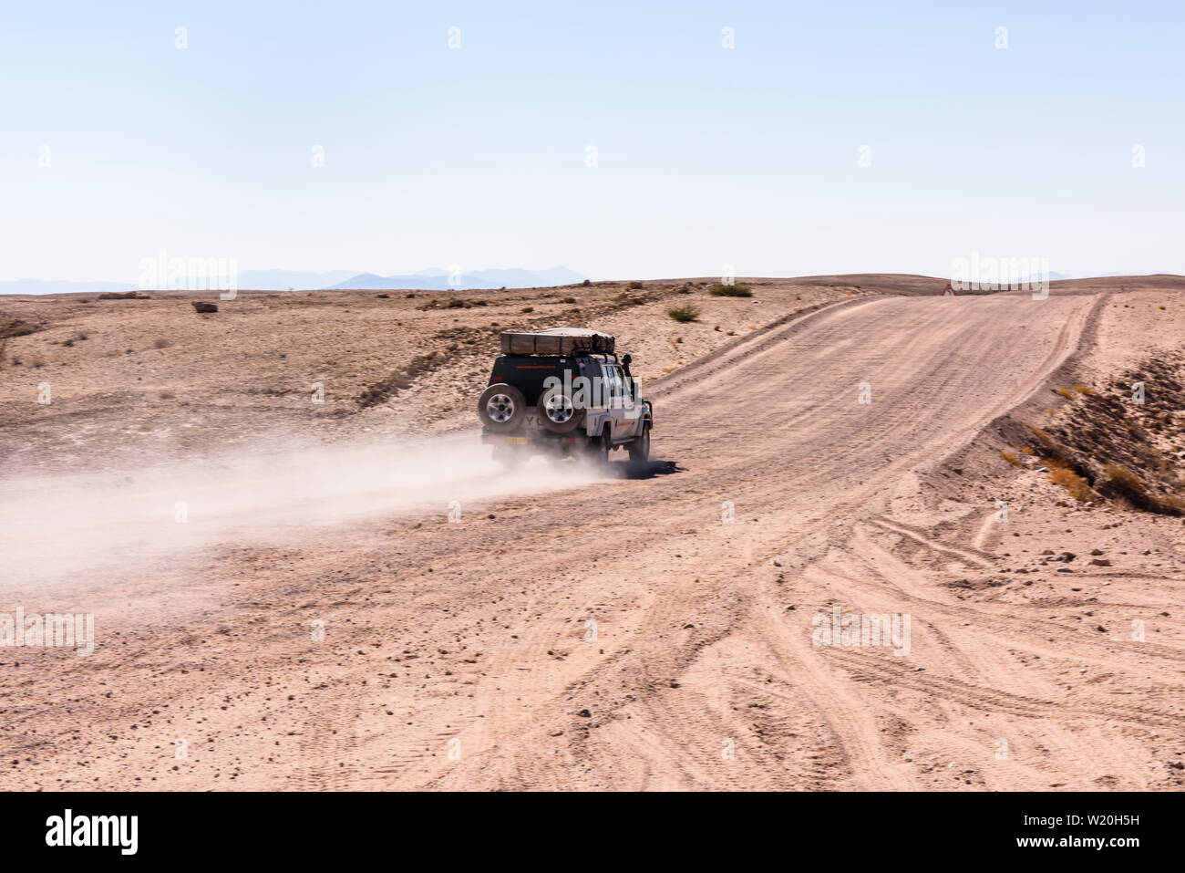 Toyota Hilux drives along a gravel dirt road leaving a dust trail in Central Namibia Stock Photo
