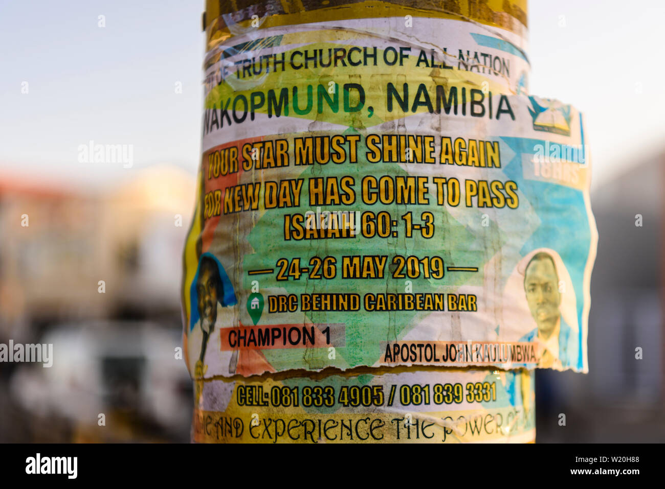 Flyer attached to a lamppost advertising an evangelical meeting in Swakopmund, Namibia. - Stock Image