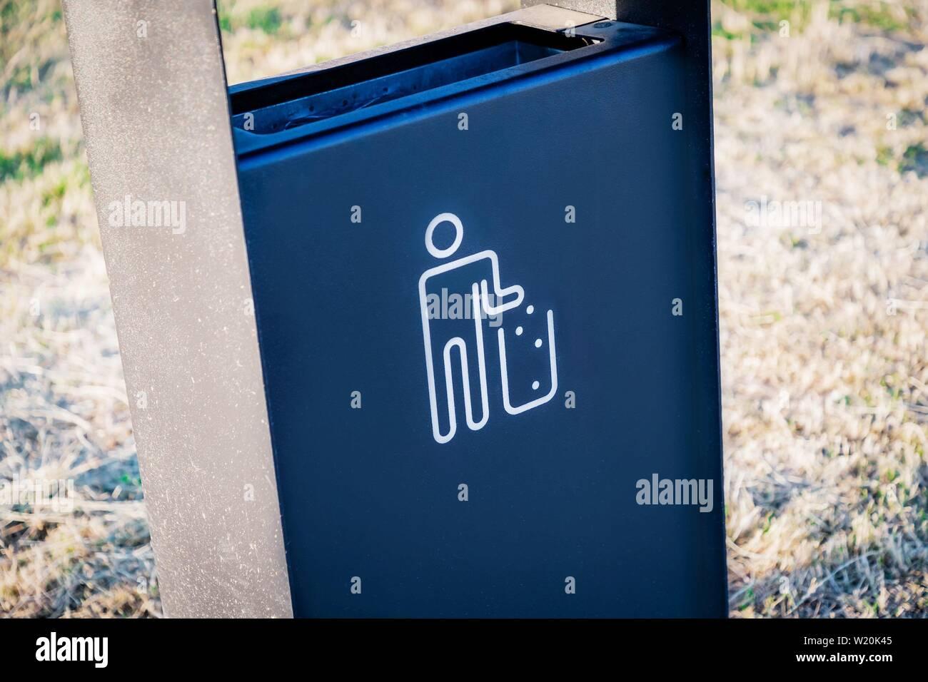 Black metal garbage bin or trash can with tidy man symbol outdoor - Stock Image