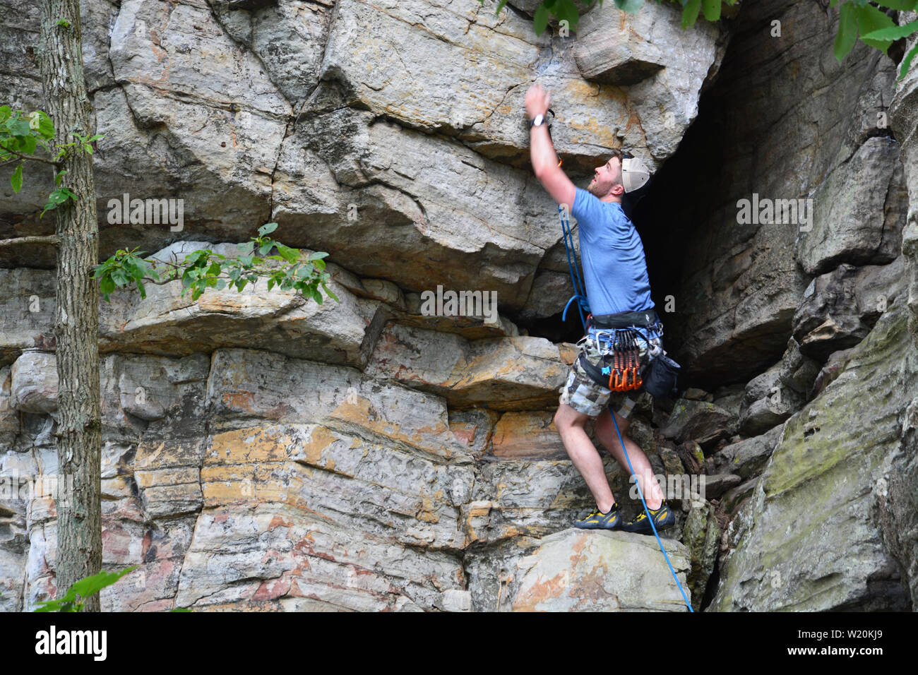A young male climber works his way up a cliff face on the Ledge Spring Trail at Pilot Mountain State Park in North Carolina. - Stock Image