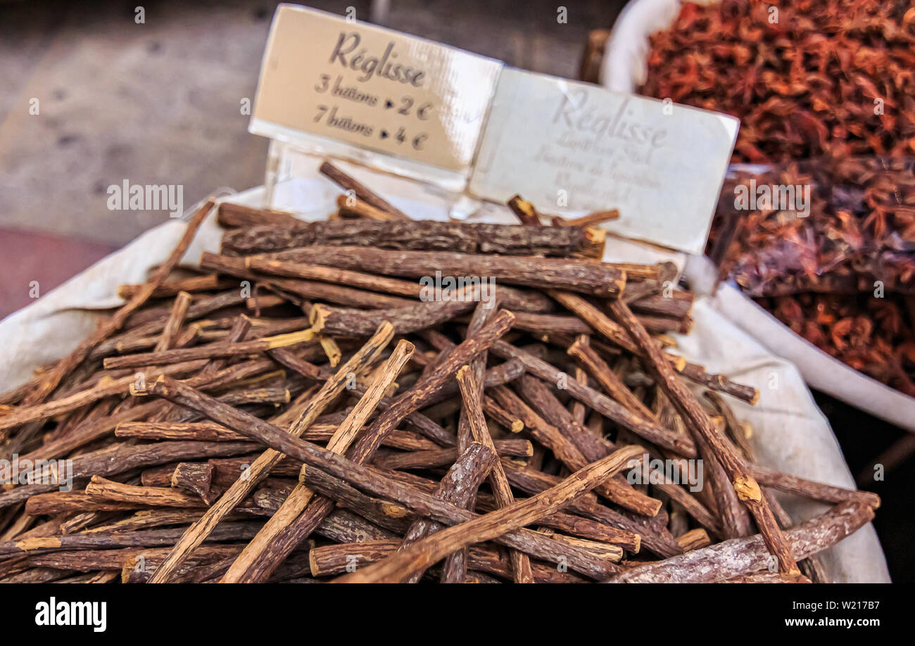 Liquorice root sticks for sale at a local outdoor farmers market with a sign advertising 3 sticks for 2 or 7 for 4 EUR in Cours Saleya in Nice, France - Stock Image