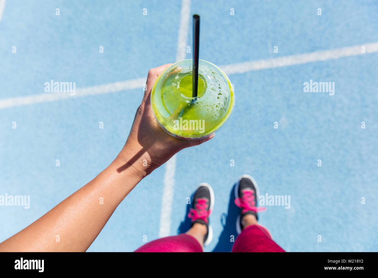 Runner drinking a healthy spinach green smoothie on outdoor running track getting ready for run. Closeup of hand holding juice drink on blue lane, social media health and fitness concept. Stock Photo