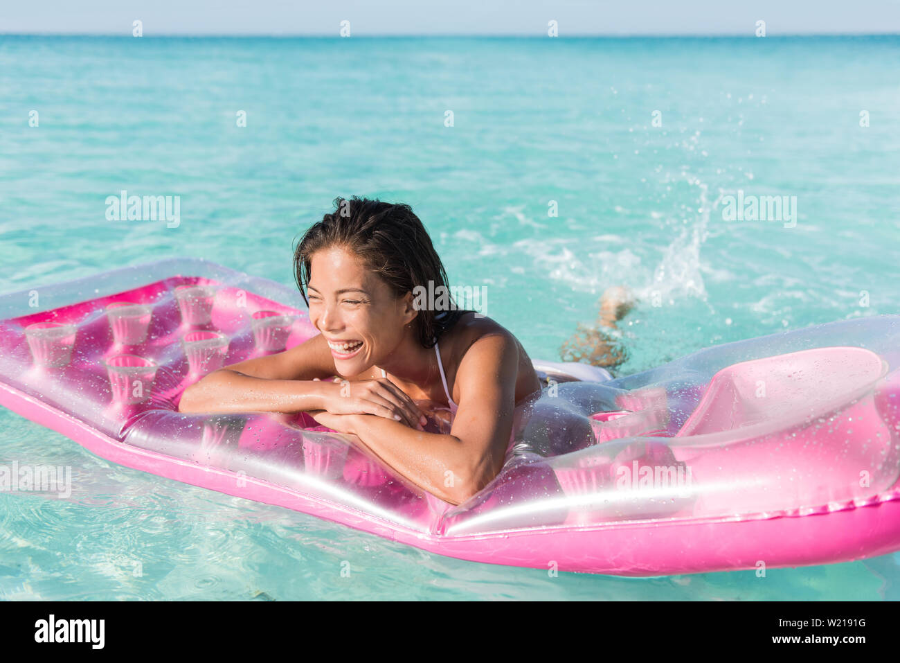 Beach girl having fun splashing water in ocean floating on pink pool float toy air mattress. Asian woman relaxing in the sun swimming in the perfect turquoise sea at holiday resort. Stock Photo