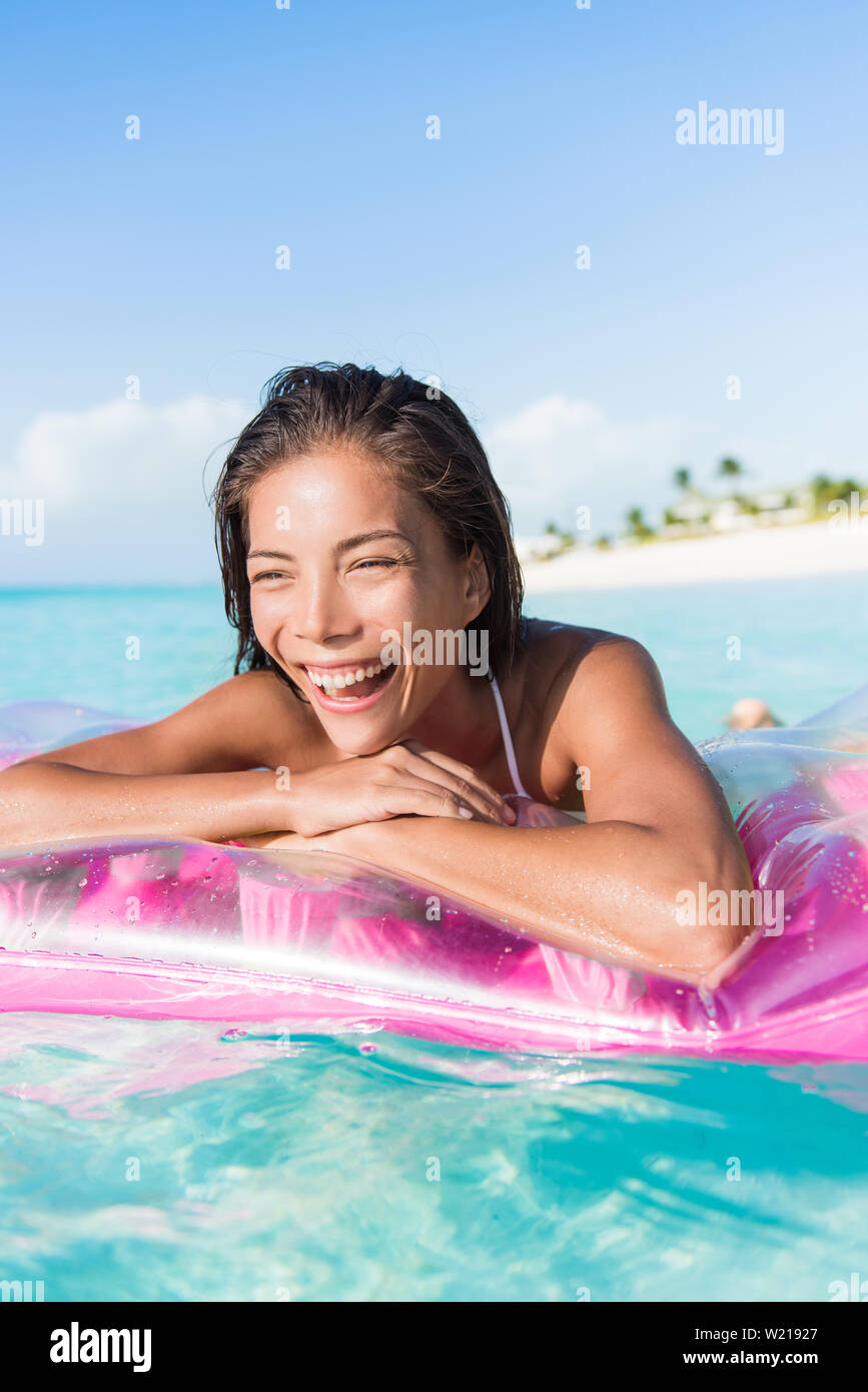 Happy beach woman swimming in ocean pristine turquoise water float air bed mattress floating toy. Asian young girl having fun with pool accessory at Caribbean holiday resort. Stock Photo