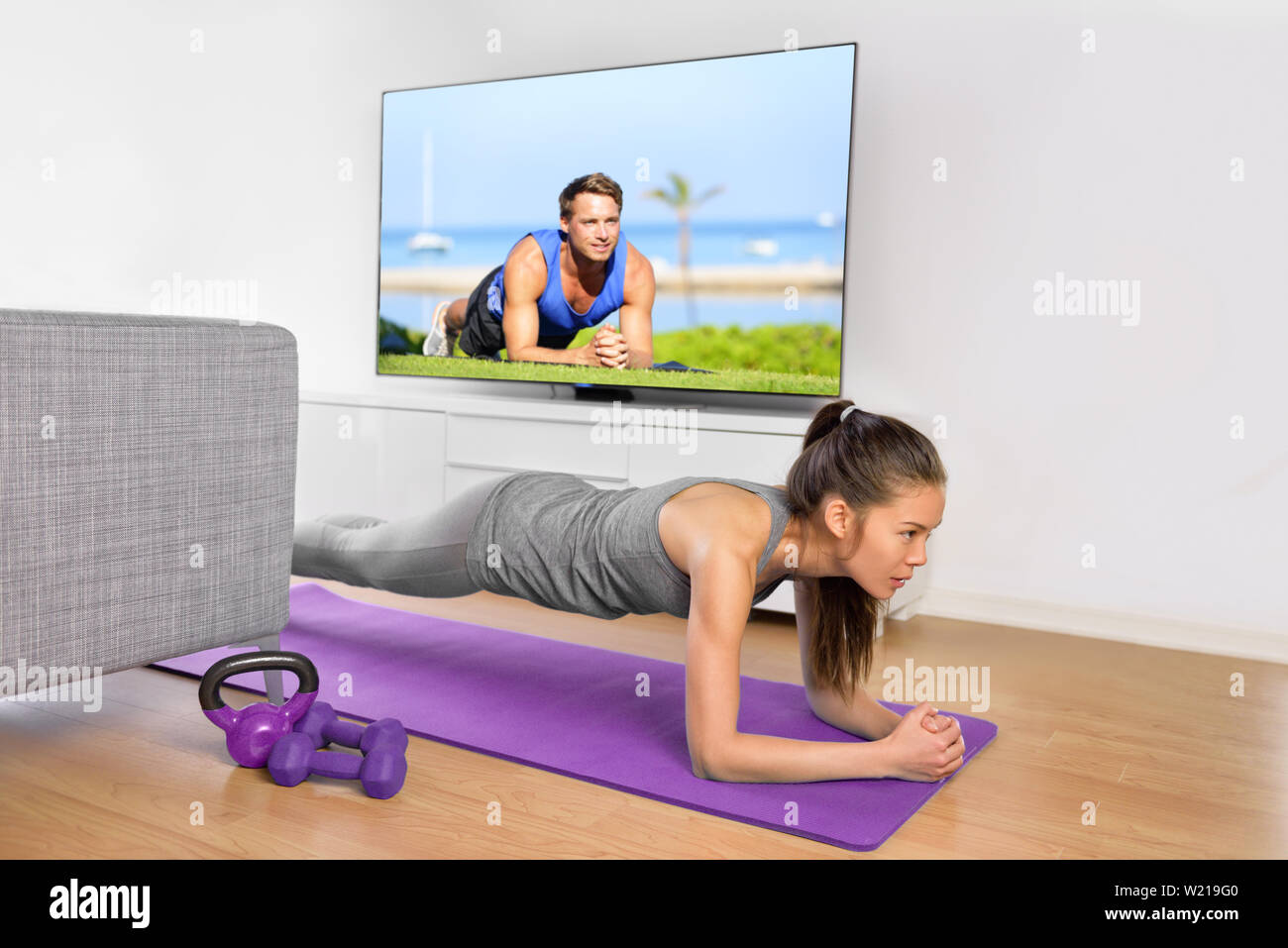 Living room fitness workout - girl doing plank exercises to exercise core at home. Young Asian woman training muscles in front of the TV as part of a healthy lifestyle without going to the gym. - Stock Image