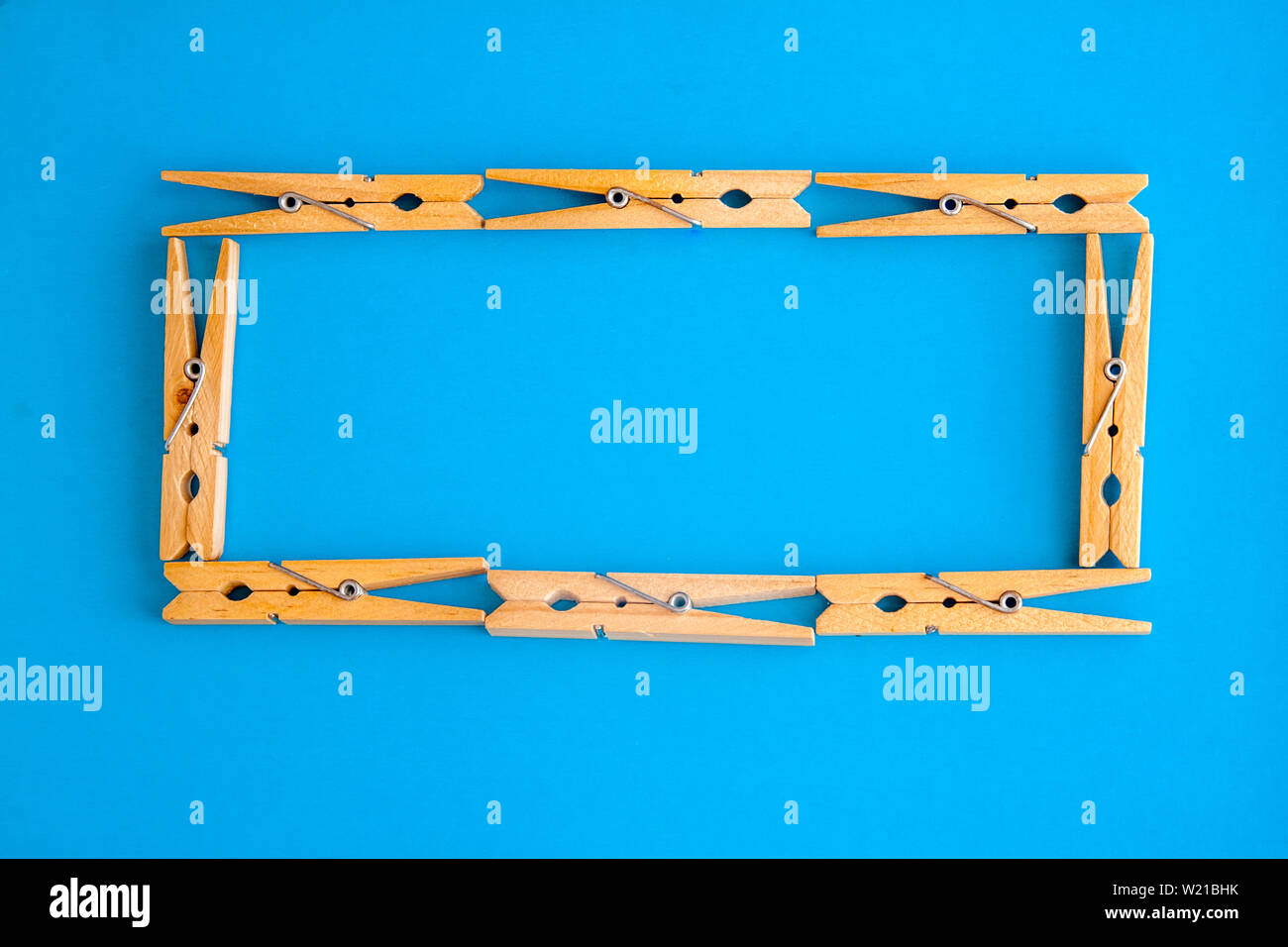 Round Or Rectangular Frame Made Of Wooden Clothespins On The Blue