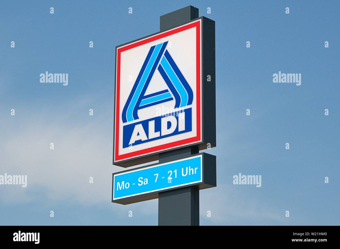30.06.2019, the nameplate on an ALDI market in Schleswig. The neon sign of the discounters with the opening hours on a stele in front of bleuem sky. | usage worldwide Stock Photo