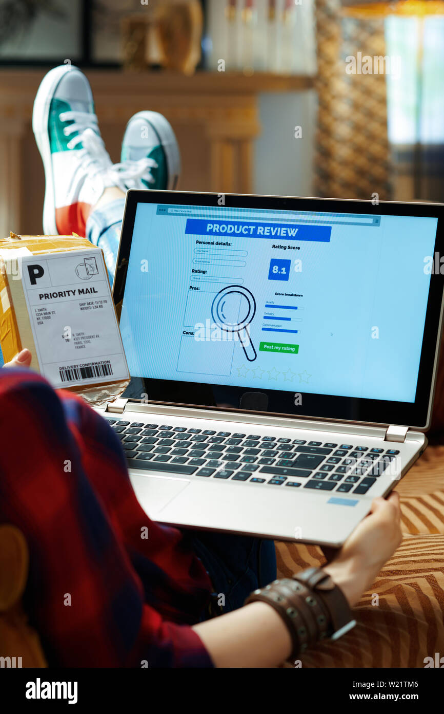 Over shoulder shot of modern hipster in red checkered shirt, jeans and sneakers with parcel writing review on laptop after online shopping while sitti - Stock Image