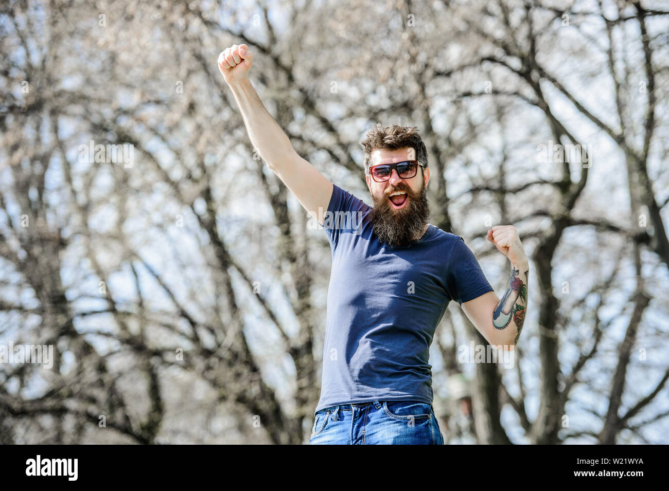 Bearded hipster brutal man wear protective sunglasses. Hipster confident in dark sunglasses. Bearded man wear modern fashionable sunglasses. UV filter. Man bearded with sunglasses nature background. - Stock Image