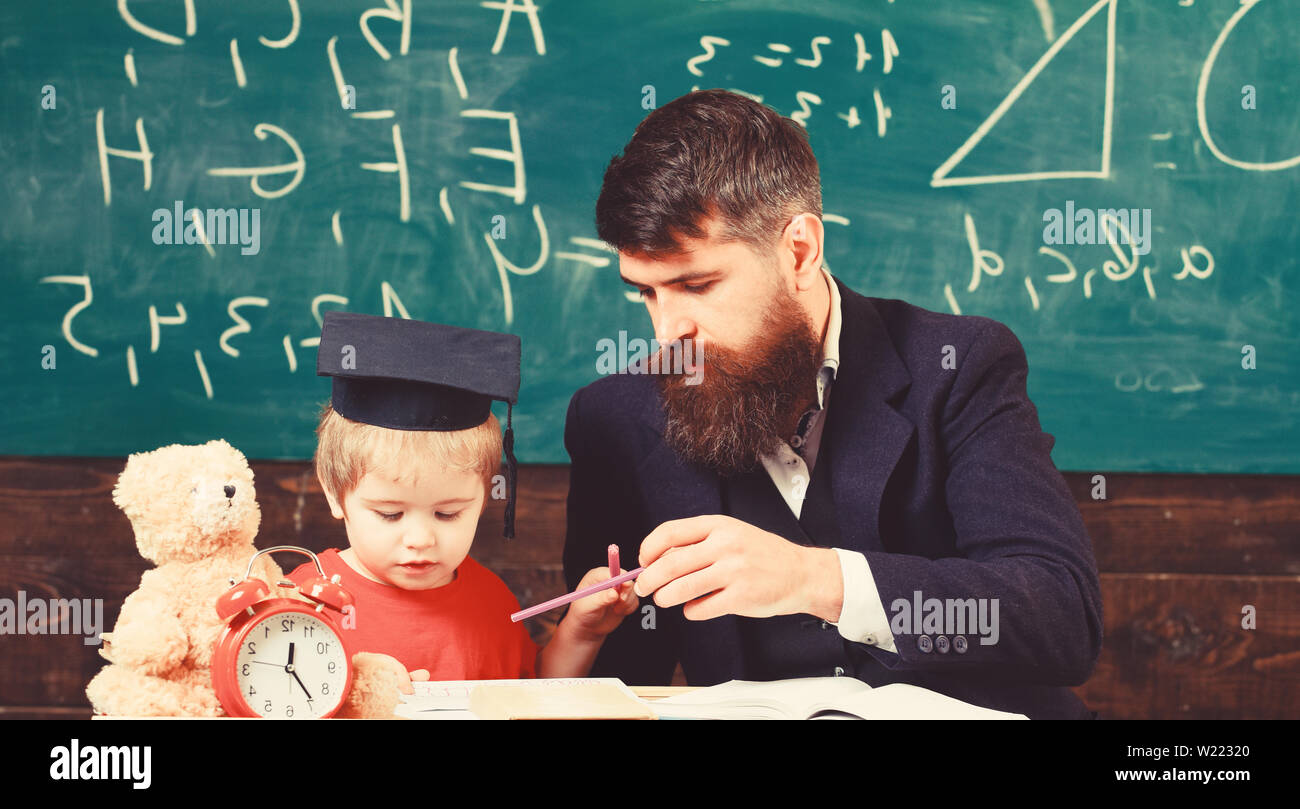 Mathematics lesson concept. Father teaches son mathematics. Teacher in formal wear and pupil in mortarboard in classroom, chalkboard on background. Enthusiastic kid studying with teacher. - Stock Image