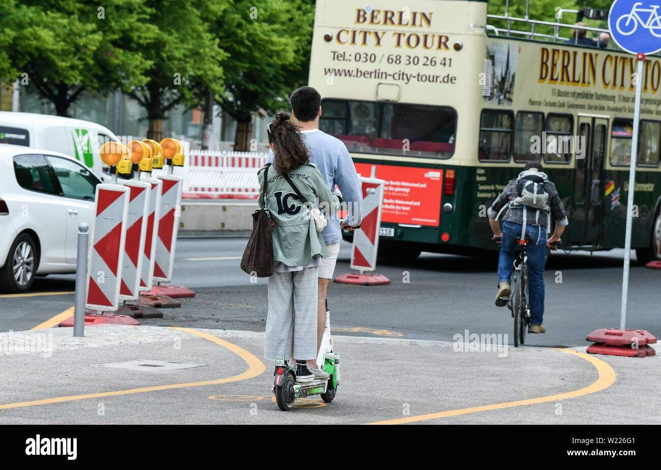 05 July 2019, Berlin: Two people drive together at the same time on an electric pedal scooter. E-scooters may be used in Germany since mid-June. Photo: Jens Kalaene/dpa-Zentralbild/ZB Stock Photo