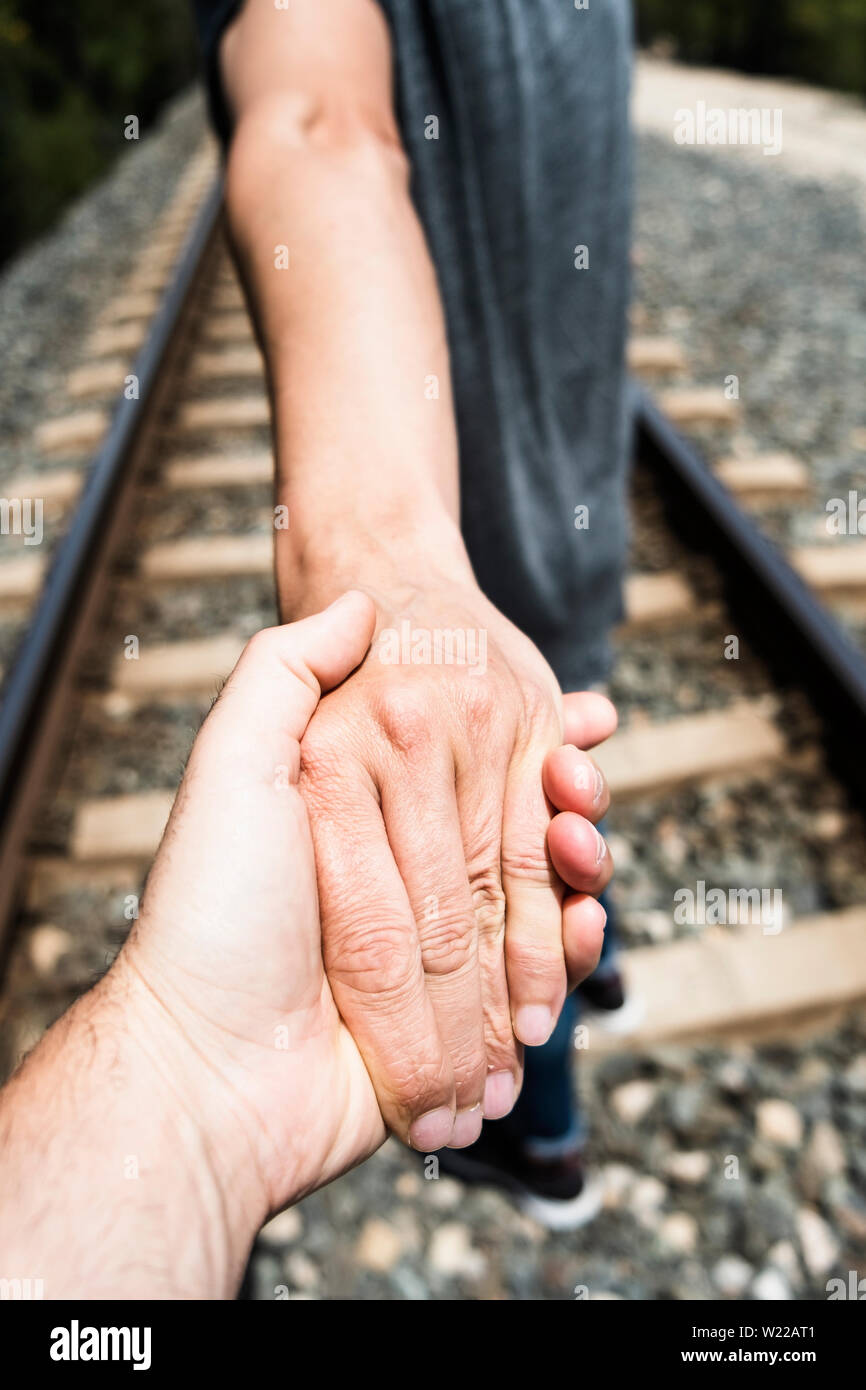 closeup of the hand of a man holding the hand of another man, seen from behind, walking by the railroad tracks on a natural landscape Stock Photo
