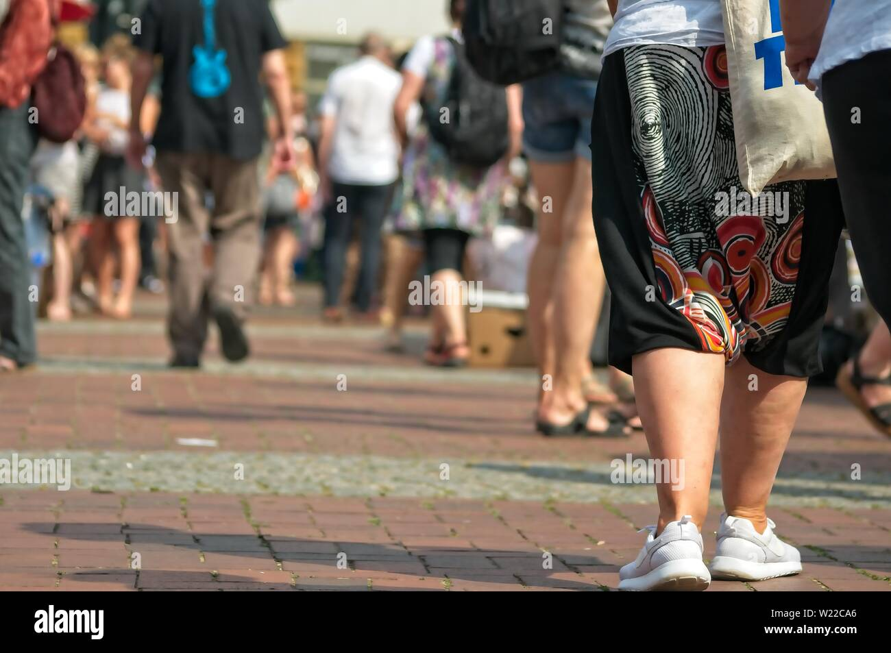 people at a weekend flea market on the streets with blurred background - Stock Image