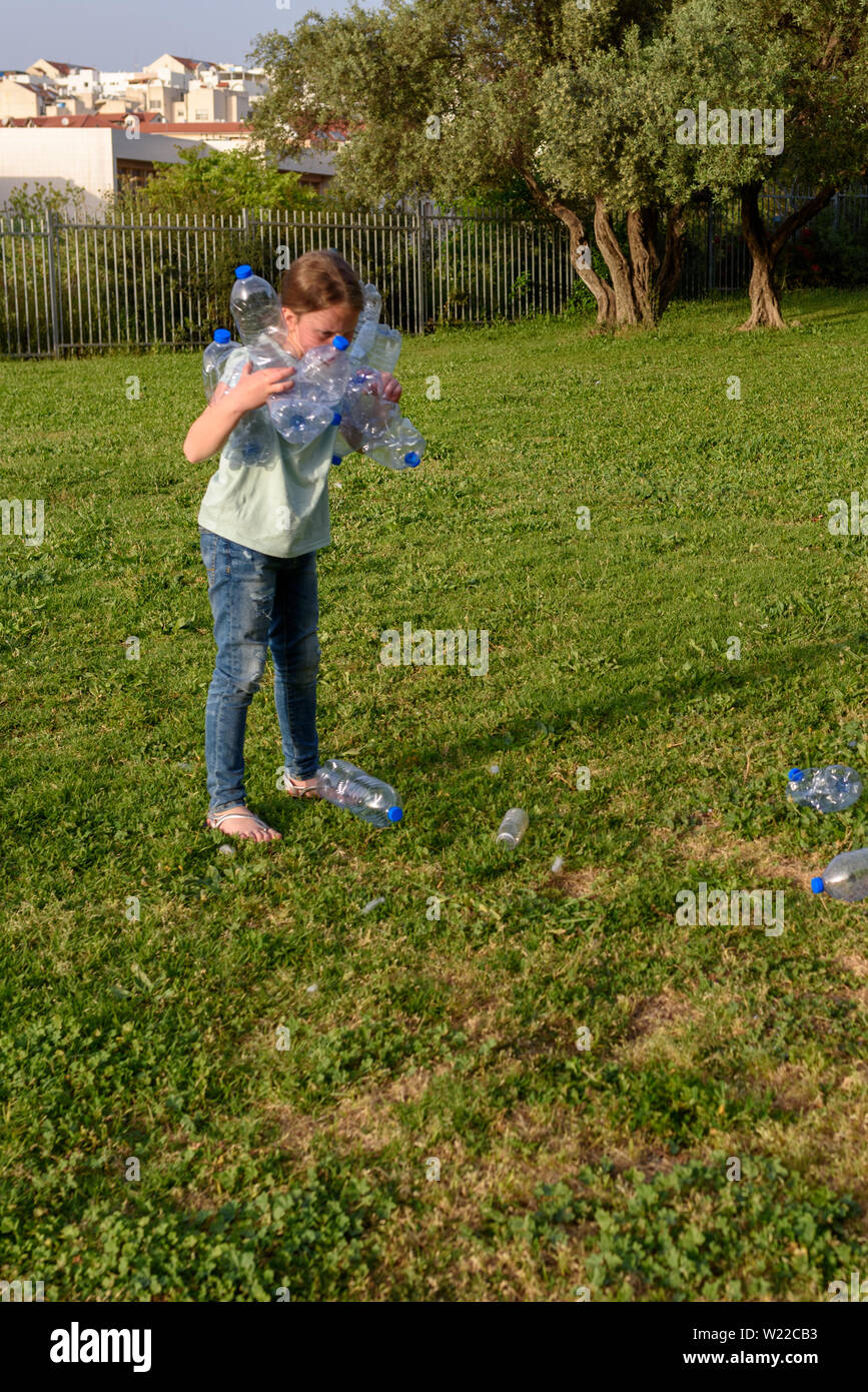 Young teenage girl recycling plastic bottles Kid volunteer