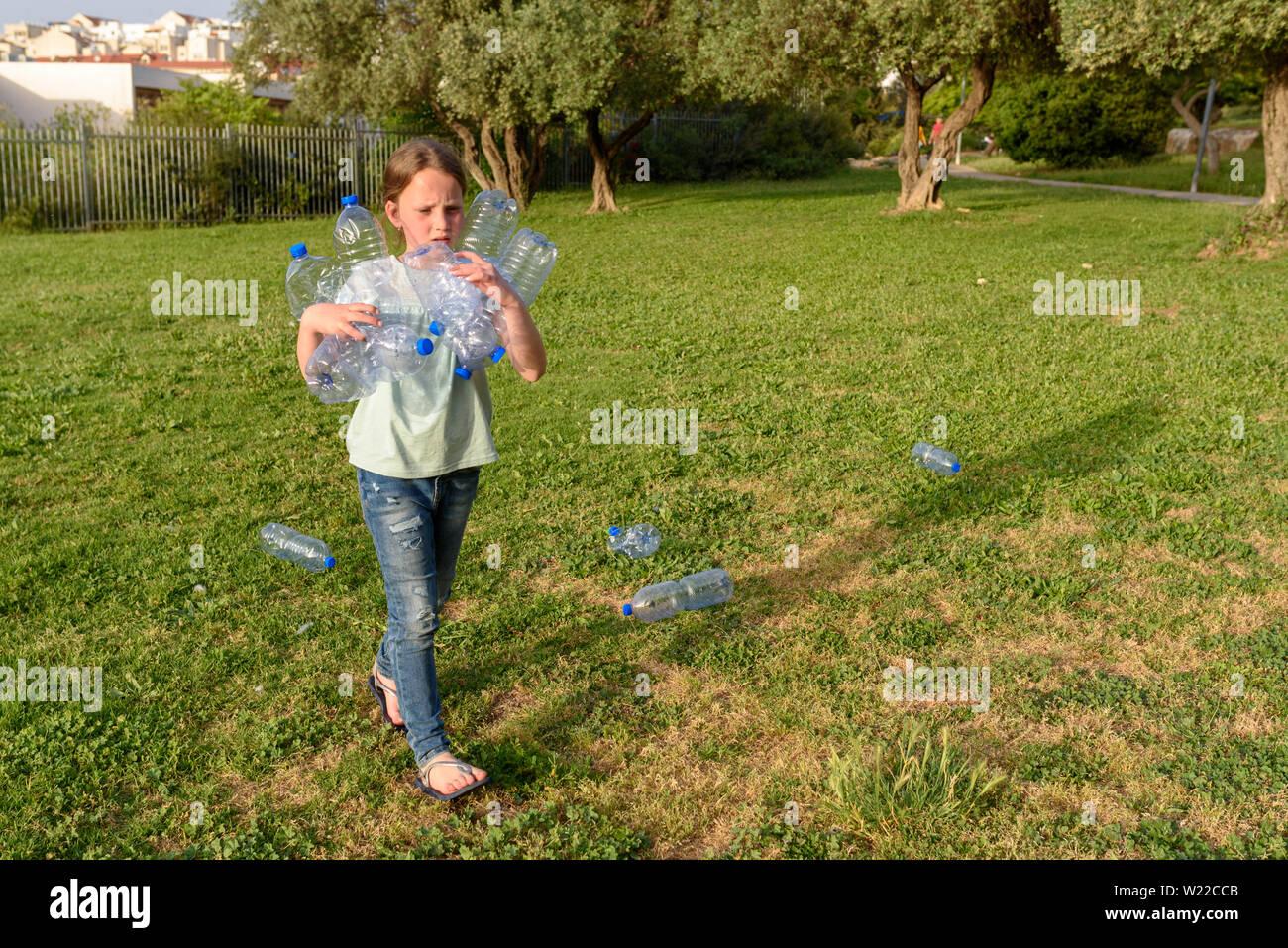 Young teenage girl recycling plastic bottles Kid volunteer cleaning