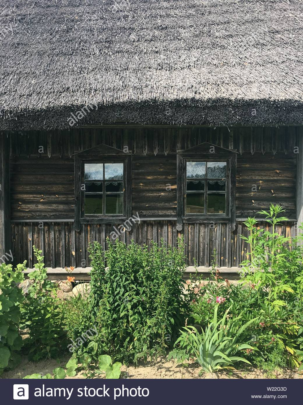 The side of an old wooden house with a straw roof - Stock Image