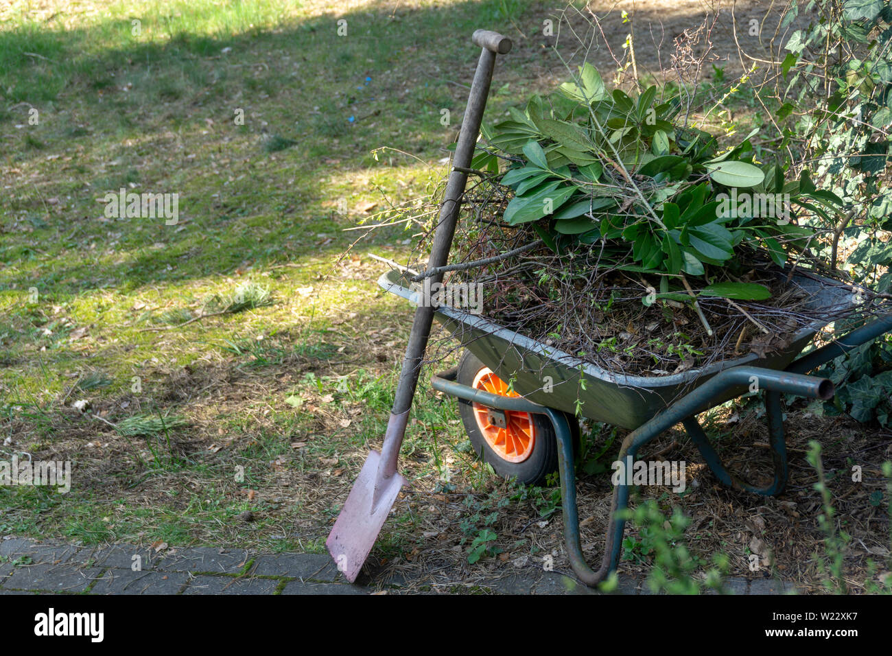 Wheelbarrow filled with leaves and branches with a fanned spade after gardening in spring, gardening Stock Photo