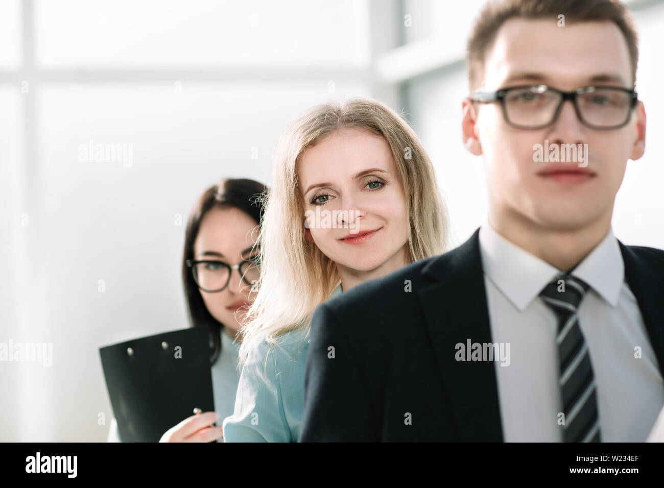 close up. young businesswoman and her colleagues standing together. photo with copy space - Stock Image