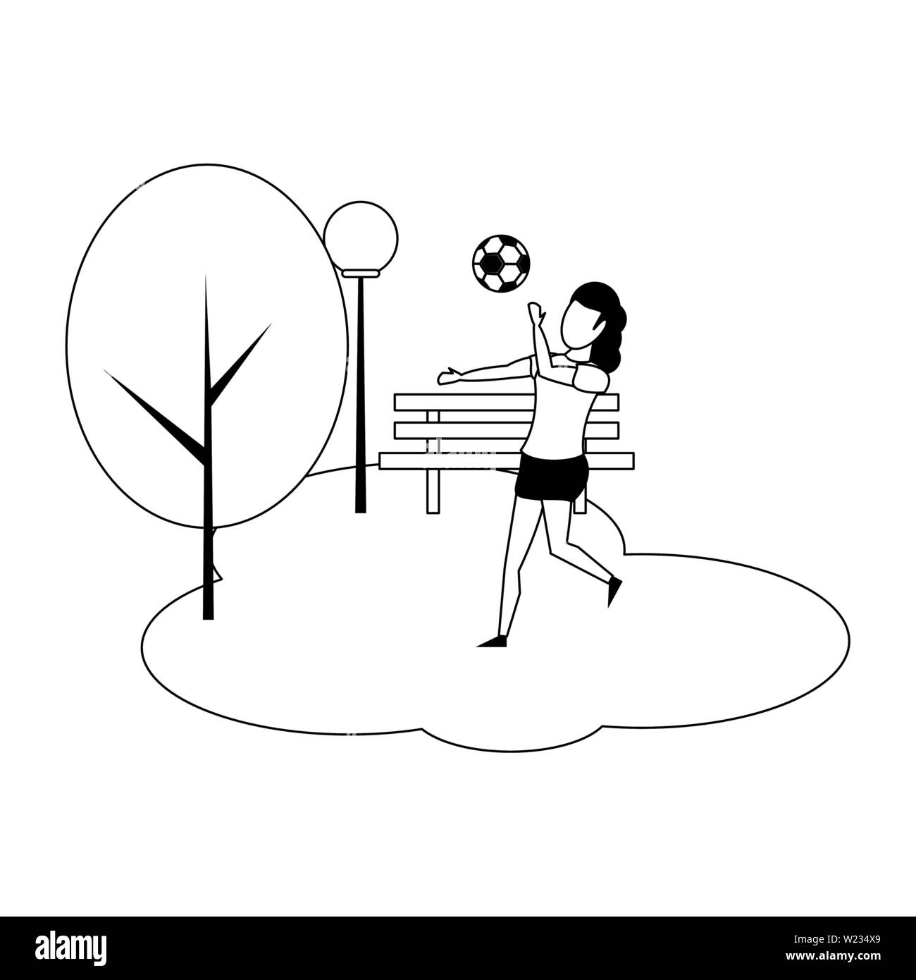 Woman playing with soccer ball at park in black and white - Stock Image
