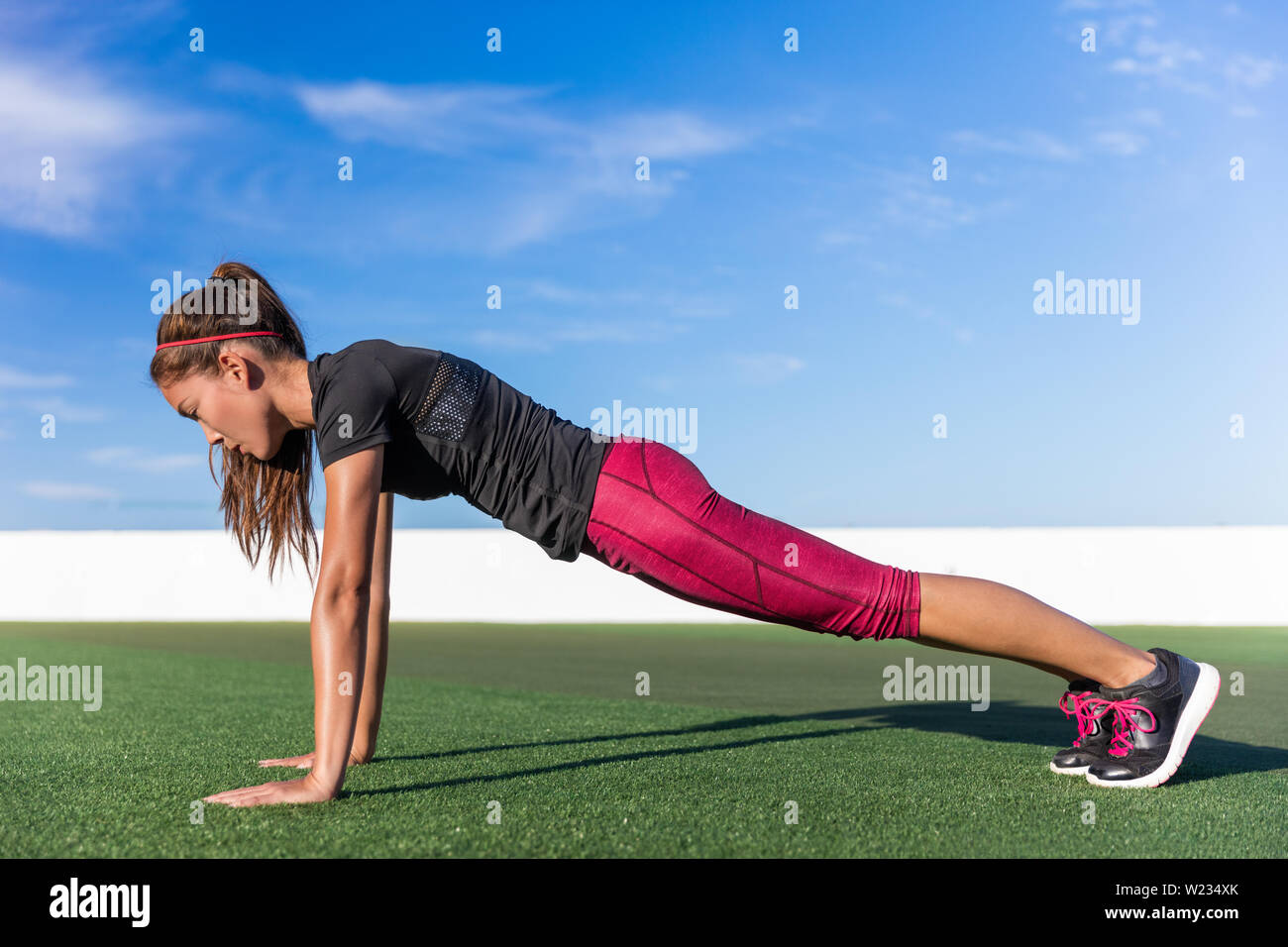 Fitness woman planking doing the bodyweight exercise for core strength training. Active girl practicing the yoga plank pose for abdominal muscles in summer outdoors living a fit life. - Stock Image