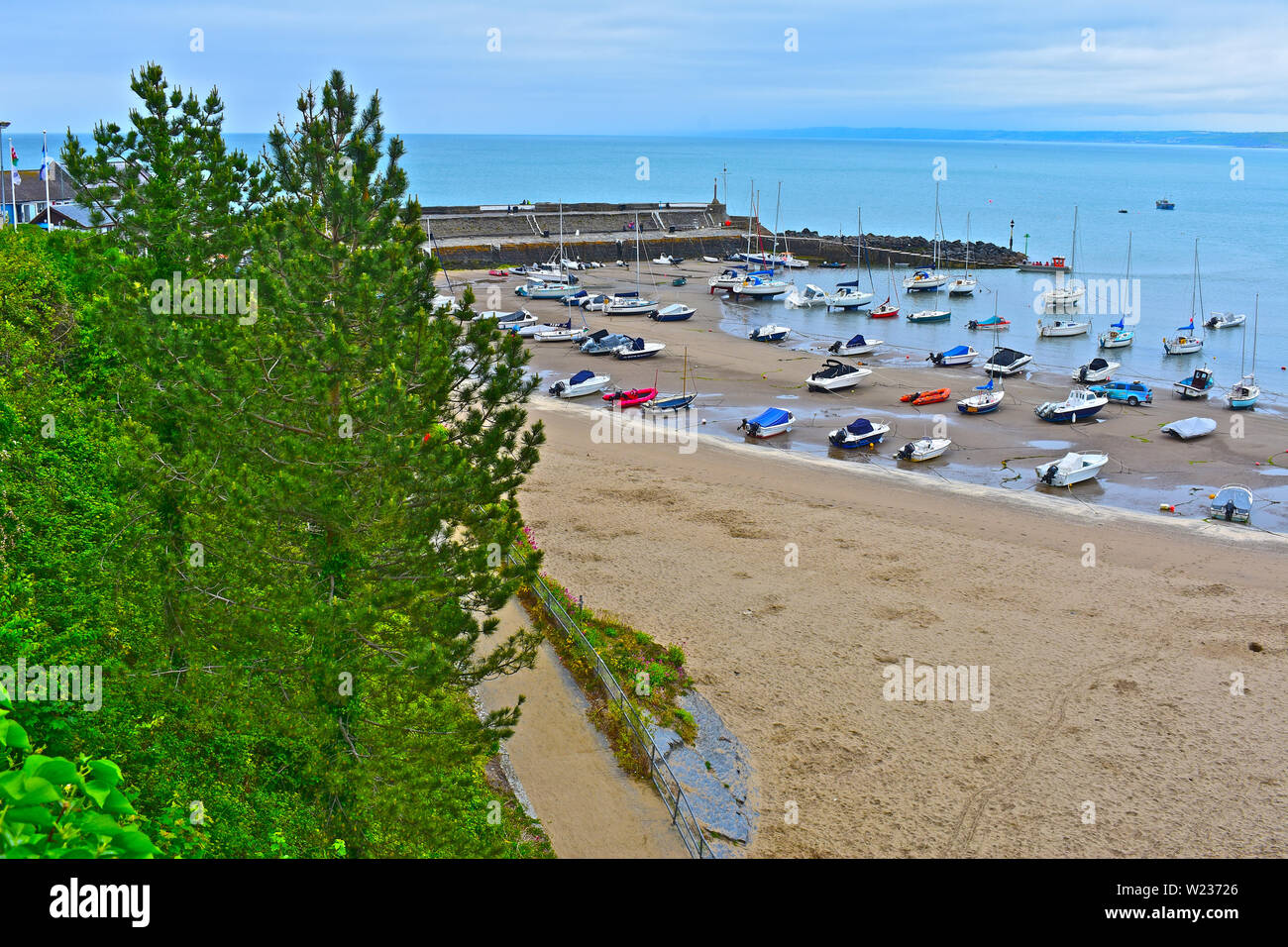 A view of the pretty little harbour at Newquay in West Wales, at low tide. Sandy beach and stone breakwater. Assorted leisure craft & fishing boats. - Stock Image