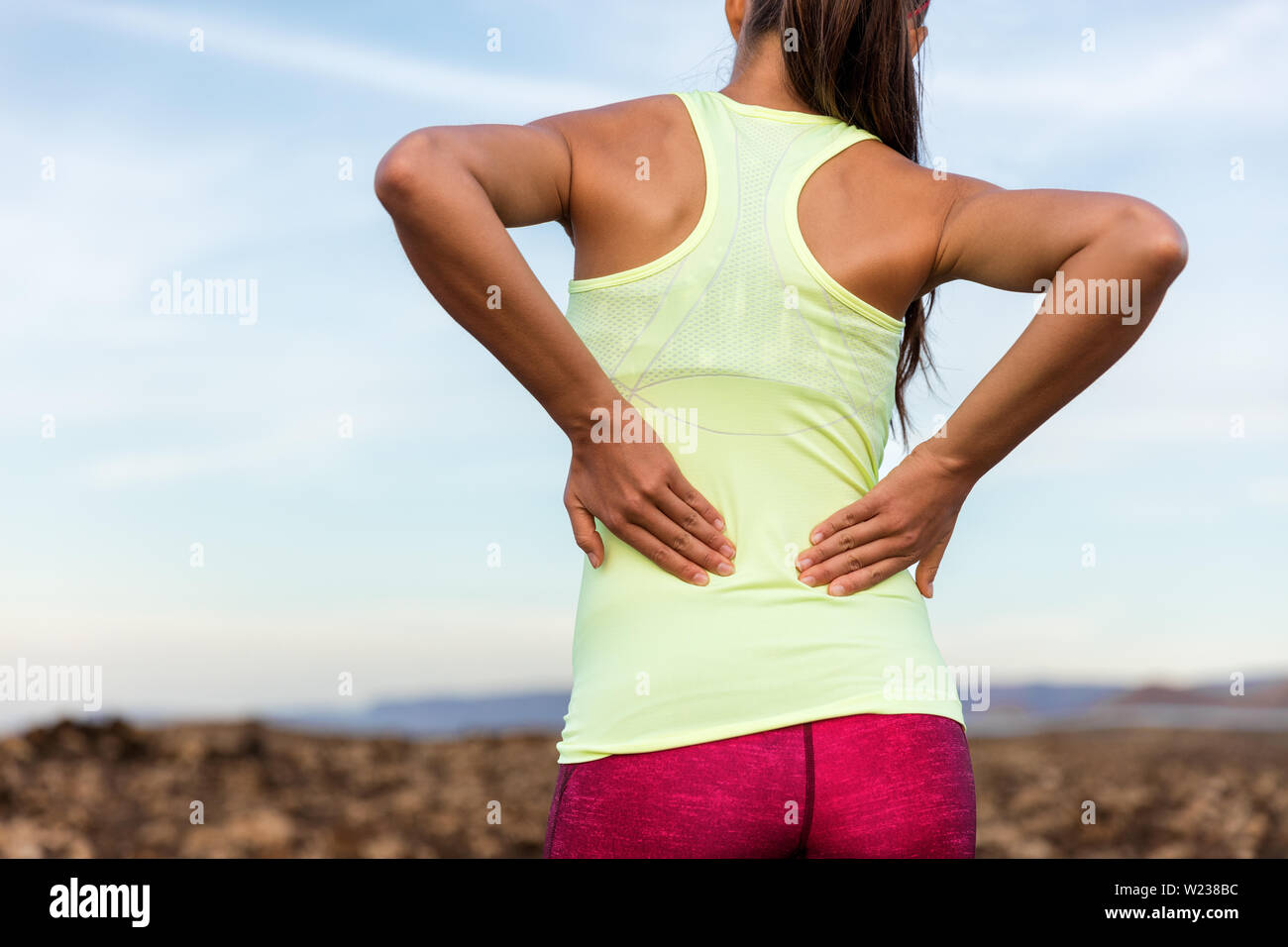 Trail running runner with painful lower back pain injury or strained muscle near the spine. Female athlete from behind on outdoor run pressing body with hands for muscles cramping soreness. - Stock Image
