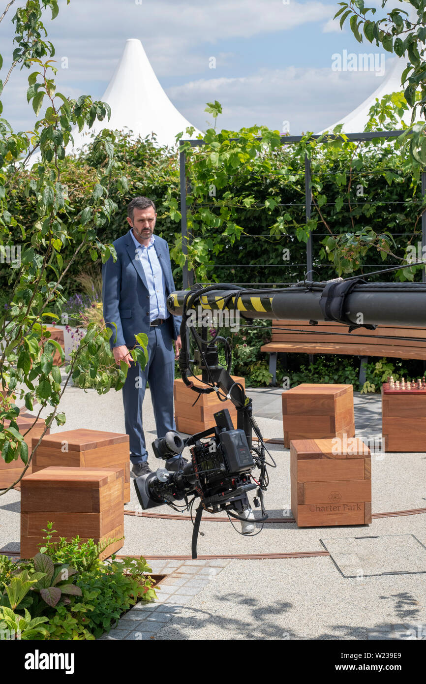 Adam Frost doing a piece to camera in a show garden at RHS Hampton Court flower show 2019. Hampton Court Palace, Surrey, UK Stock Photo