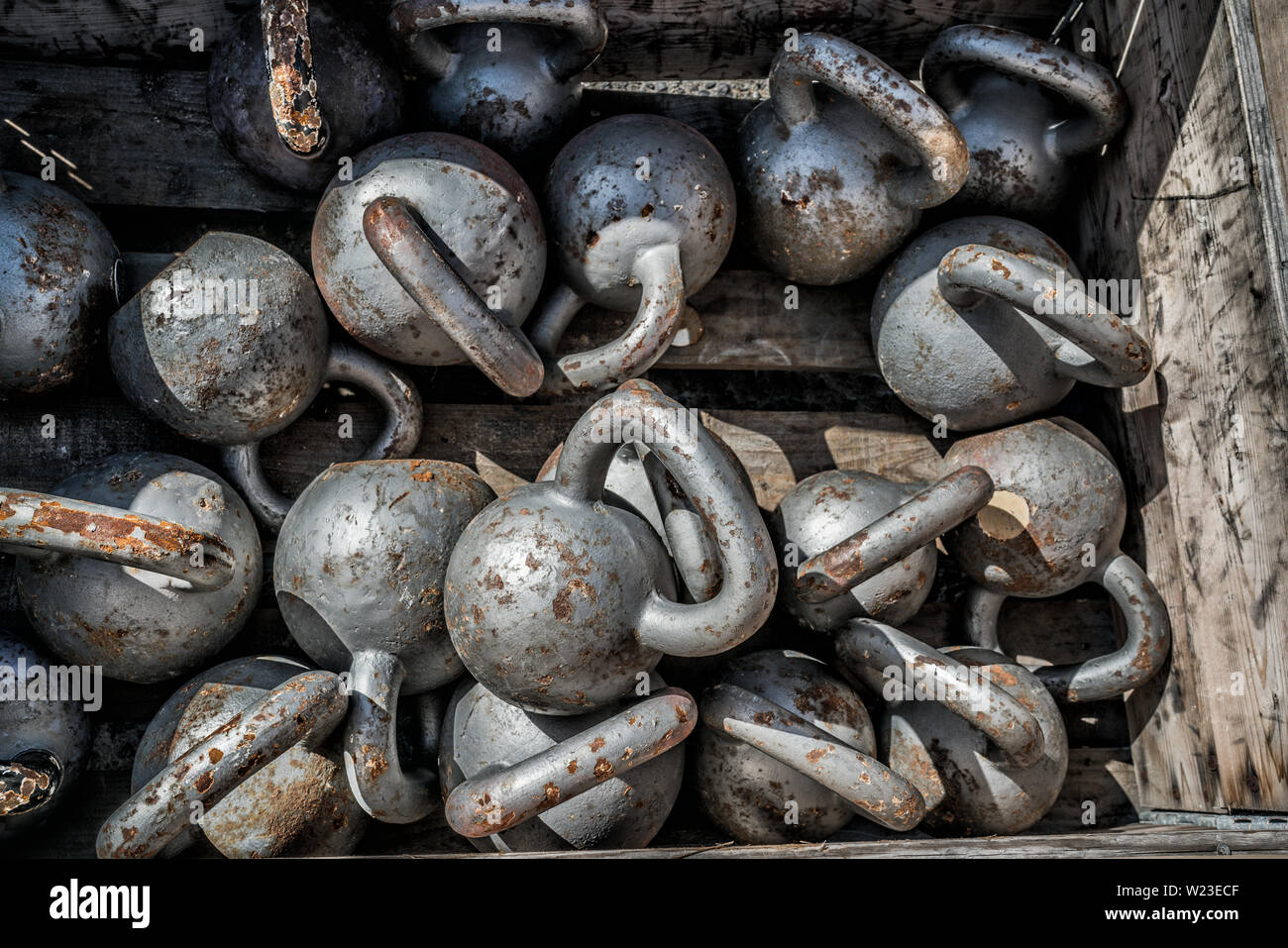 Many kettlebells weights background at outdoor gym. Texture of stell free weights for weightlifting lying on the floor at fitness center for cross training. - Stock Image