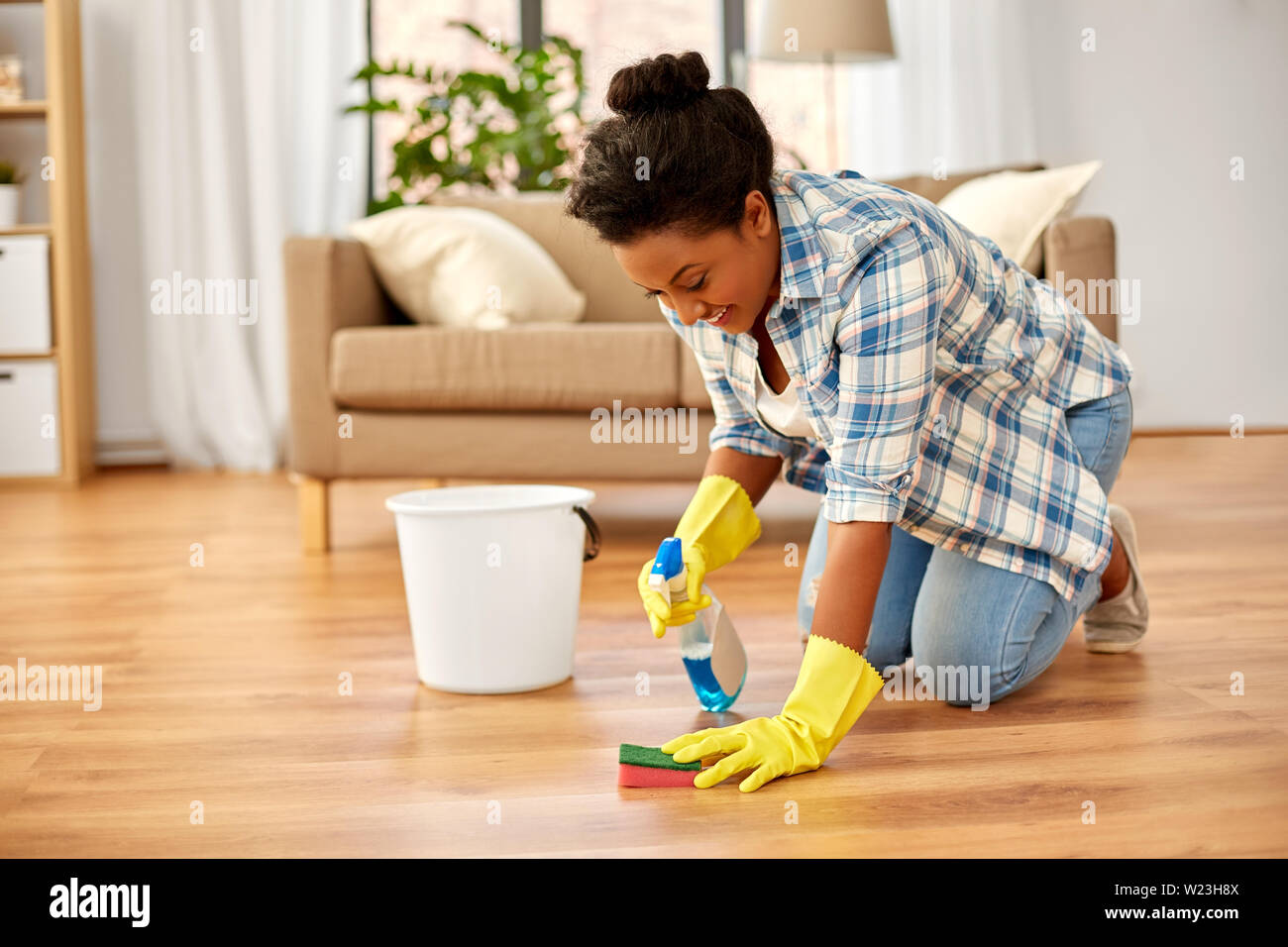 african woman with sponge cleaning floor at home - Stock Image
