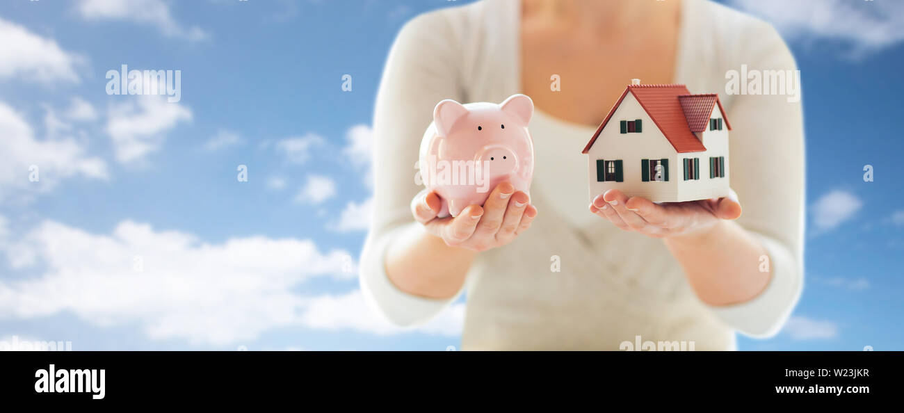 close up of woman with house model and piggy bank - Stock Image