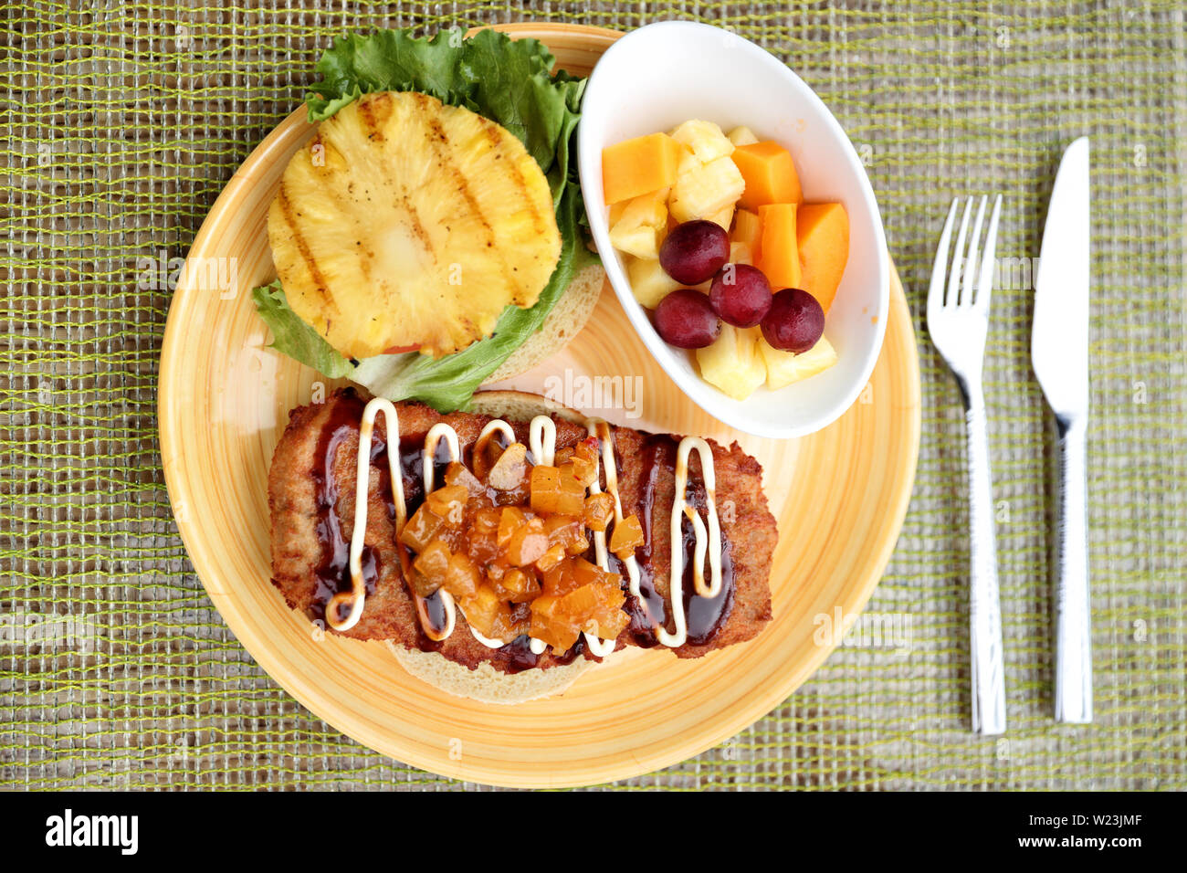Hawaiian japanese fusion food, Hawaii culture. Restaurant plate closeup of karaage chicken burger, japanese fried chicken specialty with chutney, mayonnais, grilled pineapple and fresh fruits side. - Stock Image