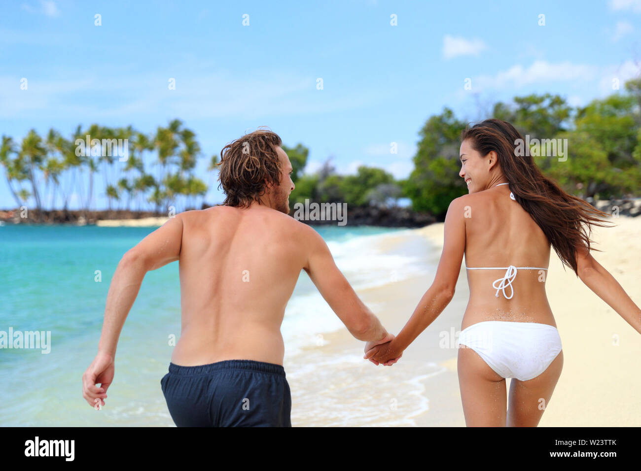 Happy couple holding hands running having fun playful on the beach. Young people from behind playing together on summer travel destination tropical holidays. Trust and relationship concept. - Stock Image