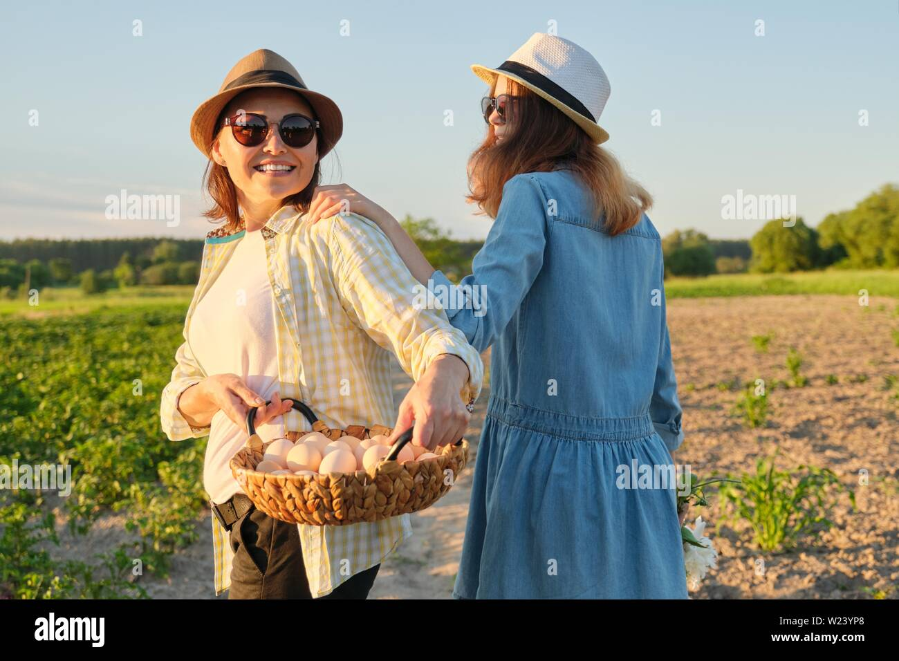 Mother and teen daughter with a basket of fresh eggs in the garden, golden hour. - Stock Image