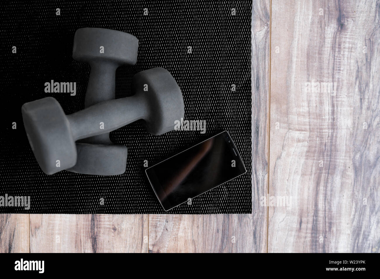 Gym fitness mat with free weights mobile phone app  Man