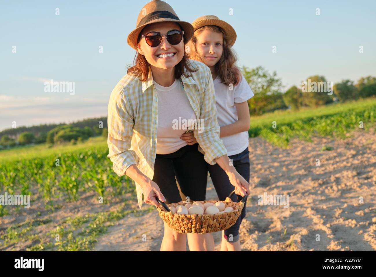 Mother and daughter with a basket of fresh eggs in the garden, golden hour. - Stock Image