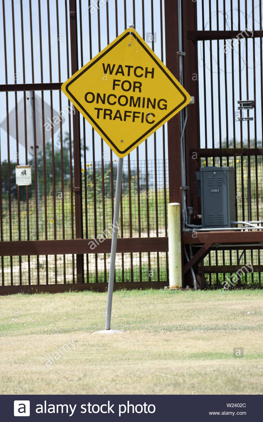 Watch for Oncoming Traffic Warning Sign at Brownsville Border Wall. Brownsville Texas Border Fence. Gate in US Mexico Border Fence. Southern Border TX Stock Photo